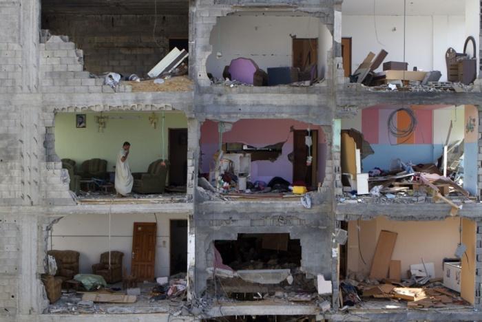 Mousa Sweidan walks around his now part demolished home in Shejaia, Gaza