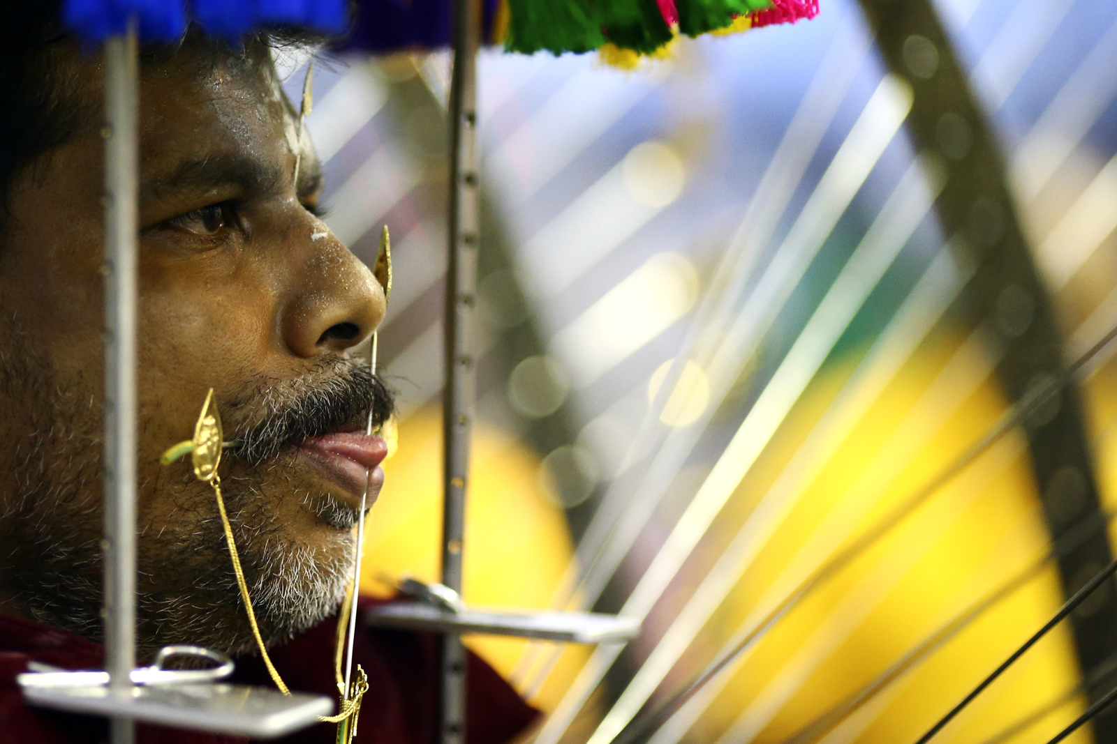 A devotee with his cheeks and tongue pierced waits to start his procession during the Thaipusam festival at the Sri Srinivasa Perumal Temple on February 9, 2017 in Singapore.