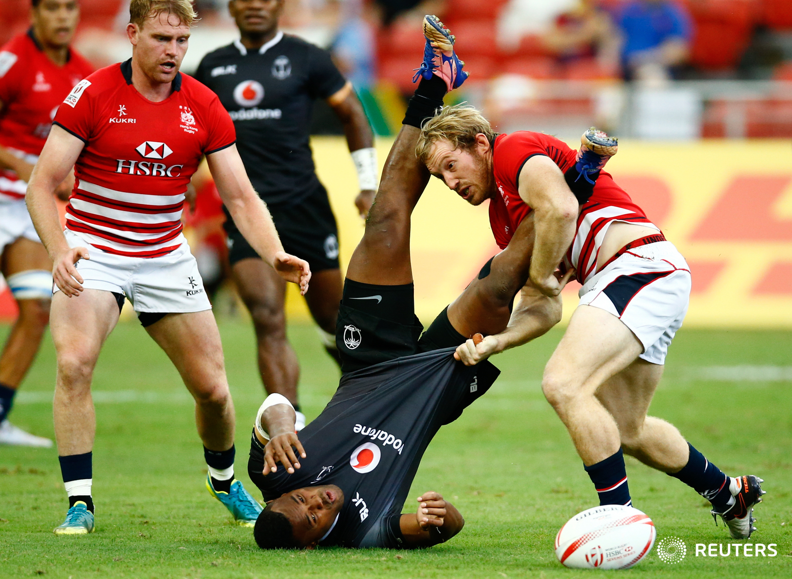 Rugby Union - Singapore Sevens - National Stadium, Singapore, 15/04/17 - Fiji's Amenoni Nasilasila is tackled by Hong Kong's Toby Fenn. REUTERS/Yong Teck Lim