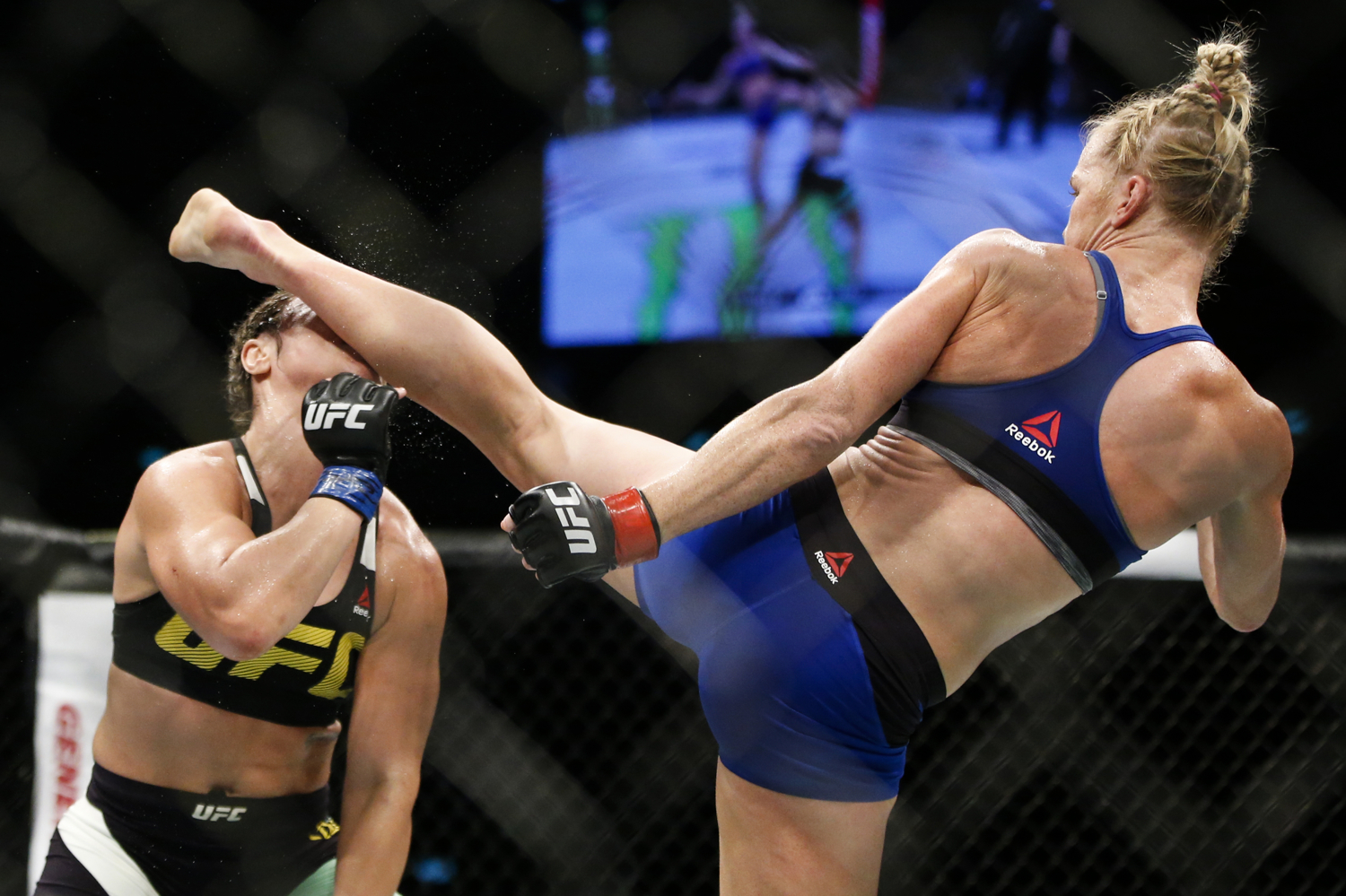 Holly Holm (R) of the United States knocks out Bethe Correia of Brazil with a kick during their bantamweight bout at the UFC Fight Night at the Singapore Indoor Stadium on June 17, 2017.