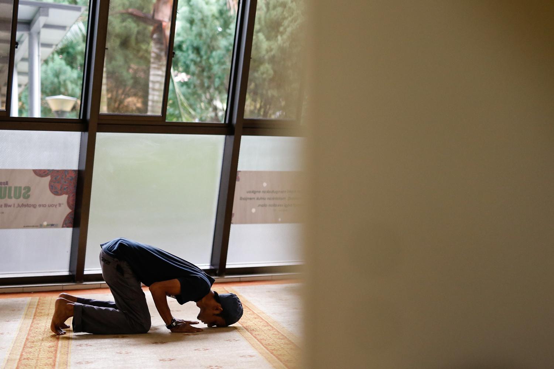 A muslim devotee prays at Masjid Al-Mukminin.