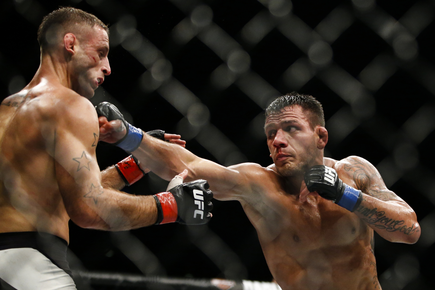 Rafael dos Anjos (R) of Brazil punches Tarec Saffiedine of Belgium during their welterweight bout at the UFC Fight Night at the Singapore Indoor Stadium on June 17, 2017.