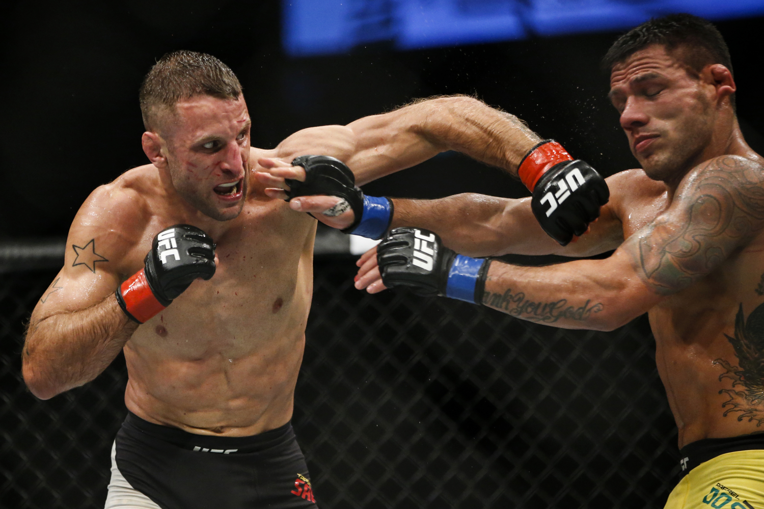 Tarec Saffiedine of Belgium (L) punches Rafael dos Anjos of Brazil during their welterweight bout at the UFC Fight Night at the Singapore Indoor Stadium on June 17, 2017.