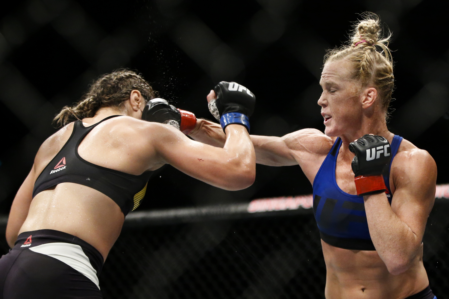 Holly Holm (R) of the United States punches Bethe Correia of Brazil during their bantamweight bout at the UFC Fight Night at the Singapore Indoor Stadium on June 17, 2017.