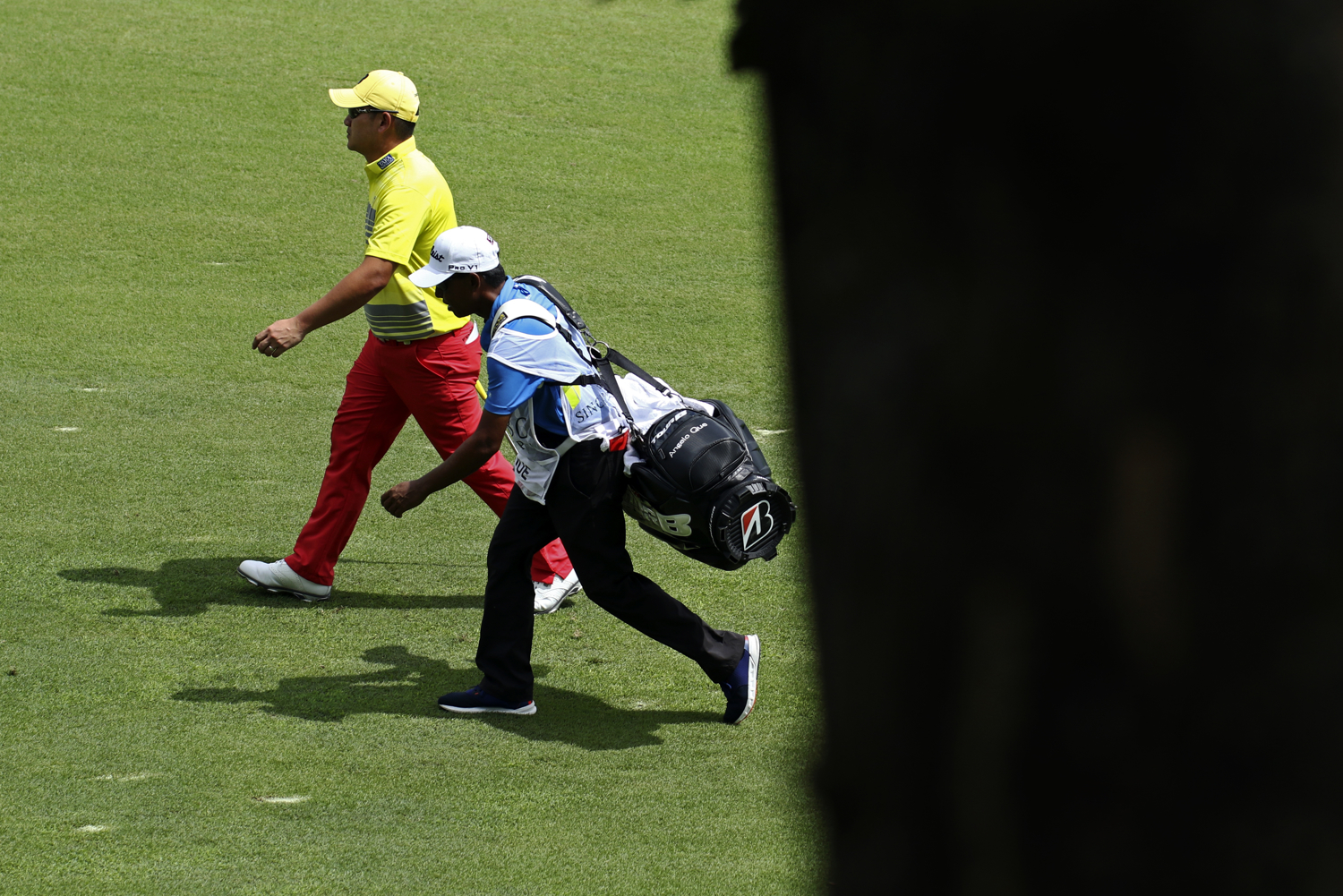 Angelo Que of the Philippines and his caddy walk on the seventh fairway during the final round of the SMBC Singapore Open golf tournament at Sentosa's Serapong golf course in Singapore January 22, 2017.