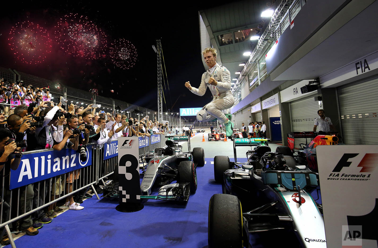 Mercedes driver Nico Rosberg of Germany jumps off his car as he celebrates after winning the Singapore Formula One Grand Prix on the Marina Bay City Circuit Singapore, Sunday, Sept. 18, 2016. (AP Photo/Yong Teck Lim)