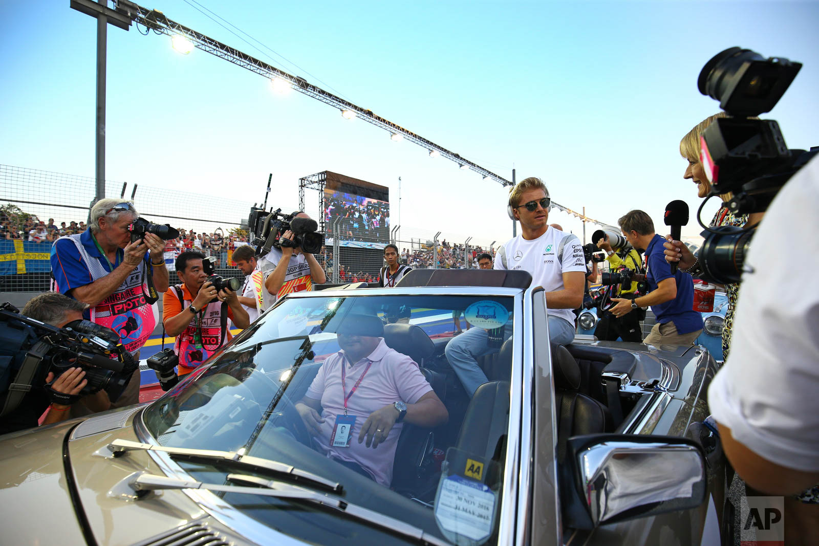 Mercedes driver Nico Rosberg of Germany sits in an open top car during the drivers parade ahead of the Singapore Formula One Grand Prix on the Marina Bay City Circuit in Singapore, Sunday, Sept. 18, 2016. (AP Photo/Yong Teck Lim)