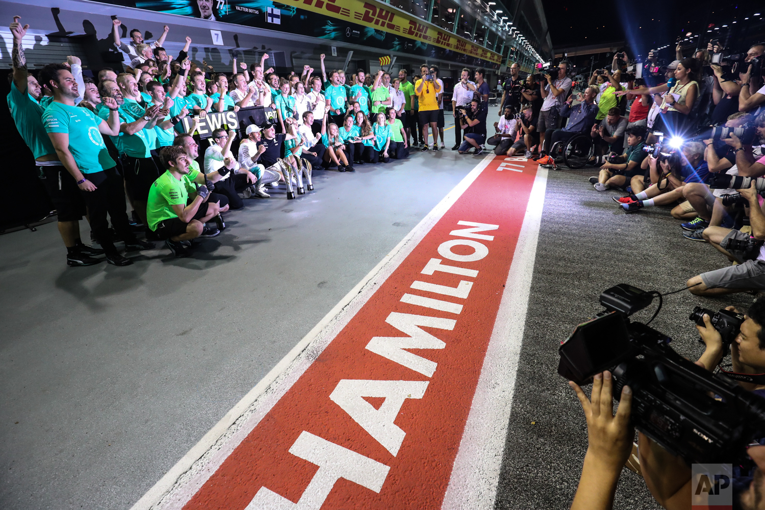 Mercedes driver Lewis Hamilton of Britain and Mercedes driver Valtteri Bottas of Finland celebrate with their team after the Singapore Formula One Grand Prix on the Marina Bay City Circuit Singapore, Sunday, Sept. 17, 2017. Hamilton won the race while Bottas finished third. (AP Photo/Yong Teck Lim)