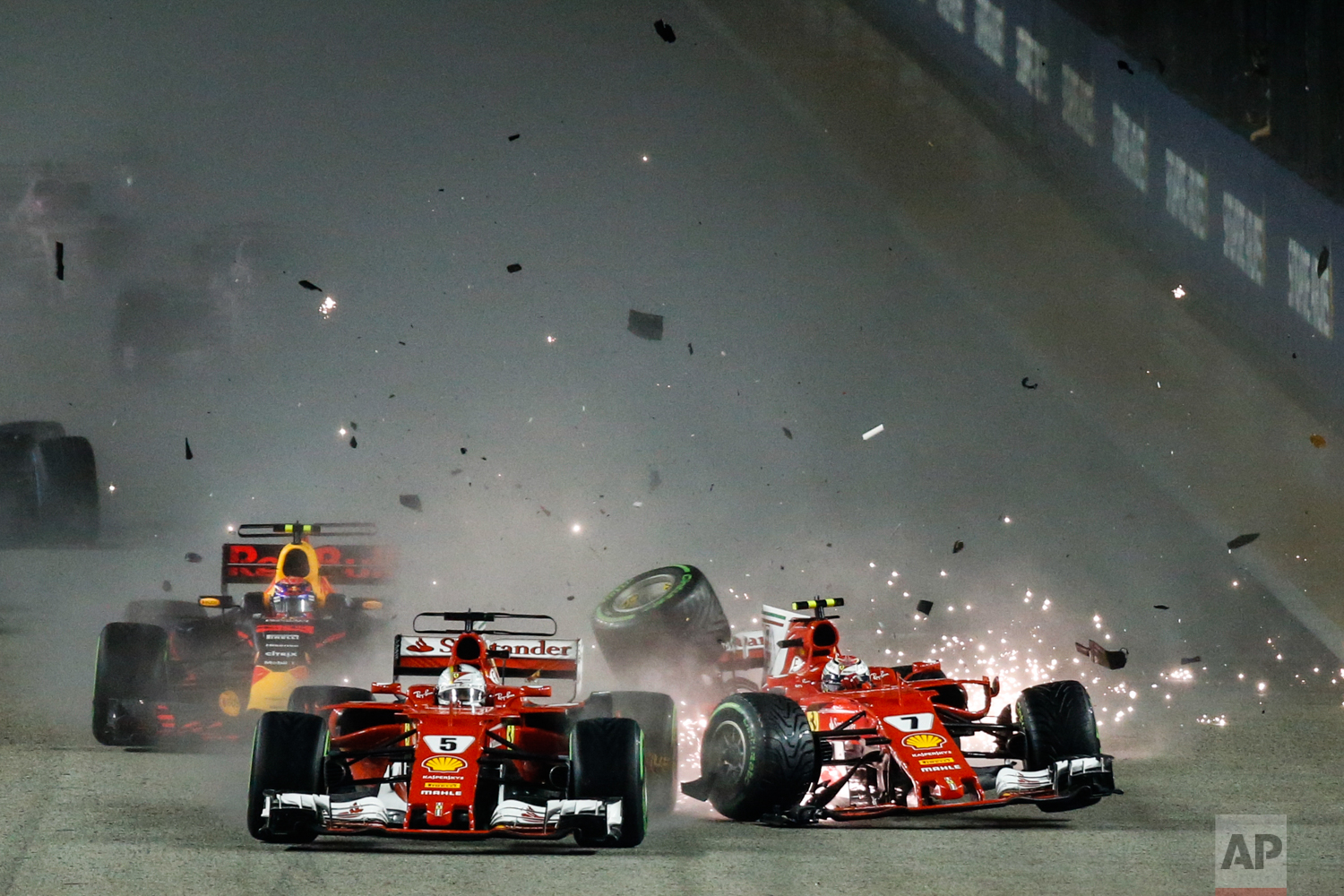 Ferrari driver Kimi Raikkonen, right, of Finland collides with teammate Sebastian Vettel of Germany at the start of the Singapore Formula One Grand Prix on the Marina Bay City Circuit Singapore, Sunday, Sept. 17, 2017. (AP Photo/Yong Teck Lim)