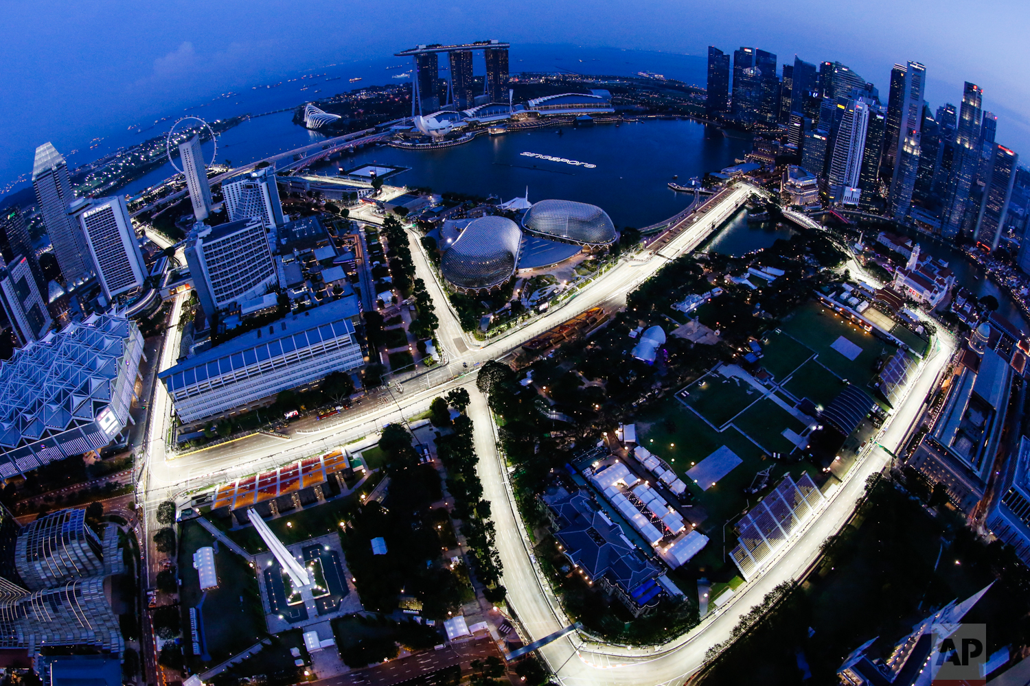 In this image made with a fisheye lens from the Swissotel The Stamford, the Singapore F1 Grand Prix's Marina Bay City Circuit is lit at dusk in Singapore on Thursday, Sept. 14, 2017. (AP Photo/Yong Teck Lim)