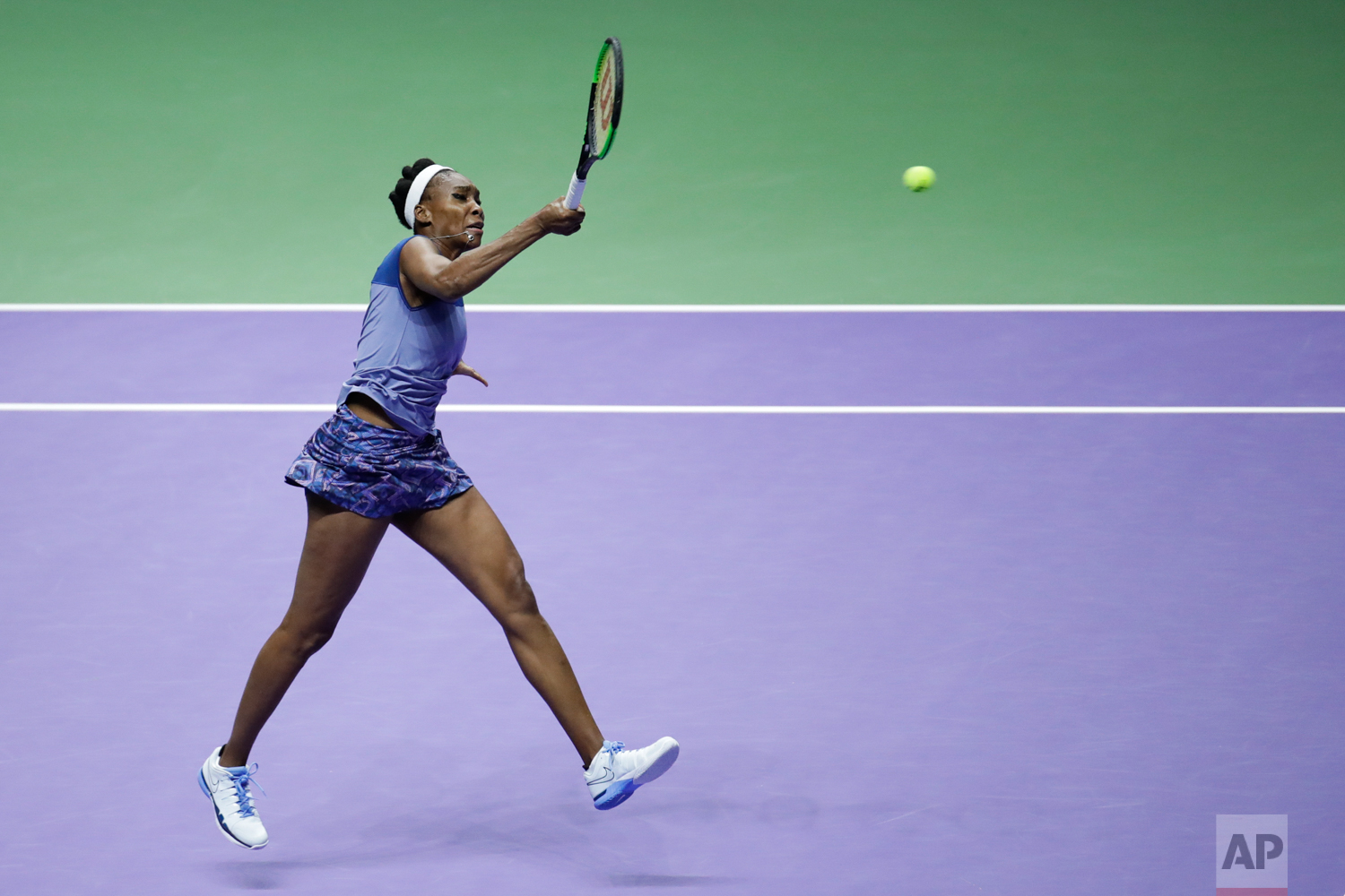 Venus Williams of the United States makes a forehand return against Caroline Wozniacki of Denmark during their singles final match at the WTA tennis tournament in Singapore, on Sunday, Oct. 29, 2017. (AP Photo/Yong Teck Lim)