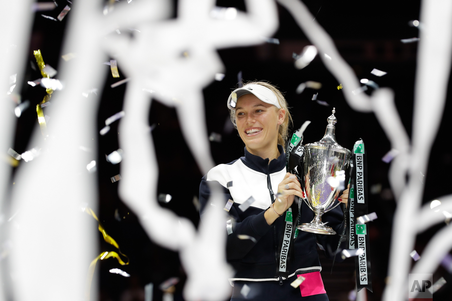 Caroline Wozniacki of Denmark lifts the winner's trophy after beating Venus Williams of the United States during their singles final match at the WTA tennis tournament in Singapore, on Sunday, Oct. 29, 2017. (AP Photo/Yong Teck Lim)