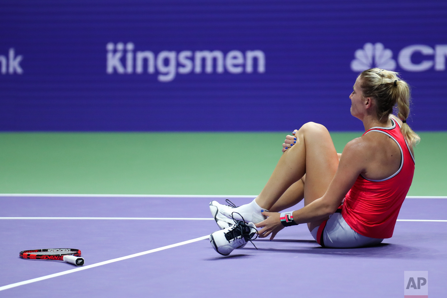 Timea Babos of Hungary, as she pairs up with partner Andrea Hlavackova of the Czech Republic, takes off her shoe after sustaining a left ankle injury during their doubles semifinal match against Martina Hingis of Switzerland and Chan Yung-Jan of Taiwan at the WTA tennis tournament in Singapore, on Saturday, Oct. 28, 2017. (AP Photo/Yong Teck Lim)
