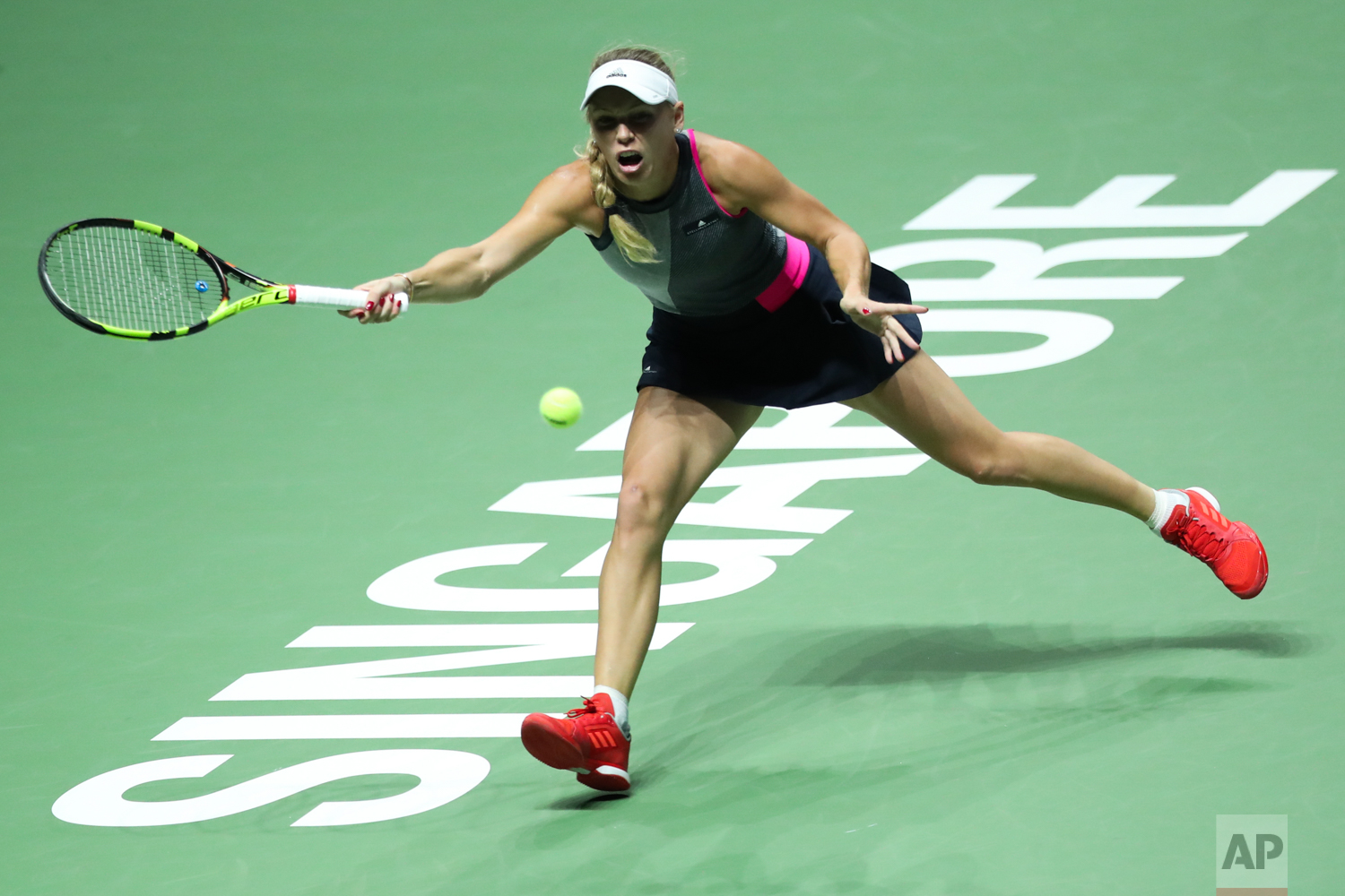 Caroline Wozniacki of Denmark makes a forehand return against Venus Williams of the United States during their singles final match at the WTA tennis tournament in Singapore, on Sunday, Oct. 29, 2017. (AP Photo/Yong Teck Lim)