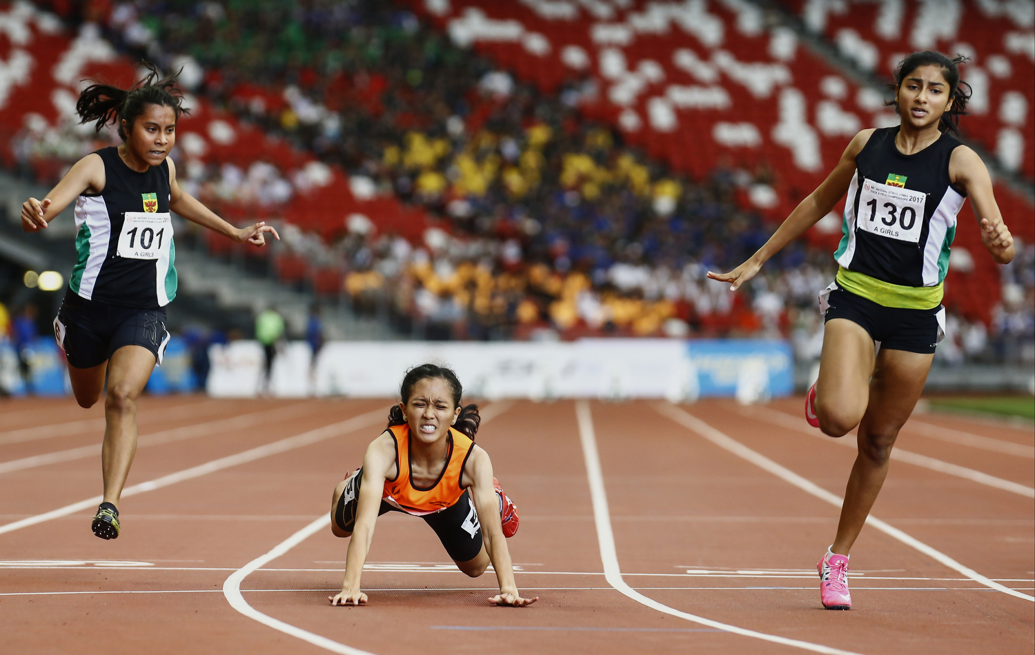 Isma Zakiah (C) of Singapore Sports School falls as she,Tanisha Moghe (R) and Amirah Aljunied (L) of Raffles Institution cross the finish line during the 'A' Division girls' 100m final during the 79th Singapore Open Track and Field Championships at the National Stadium on April 28, 2017 in Singapore.