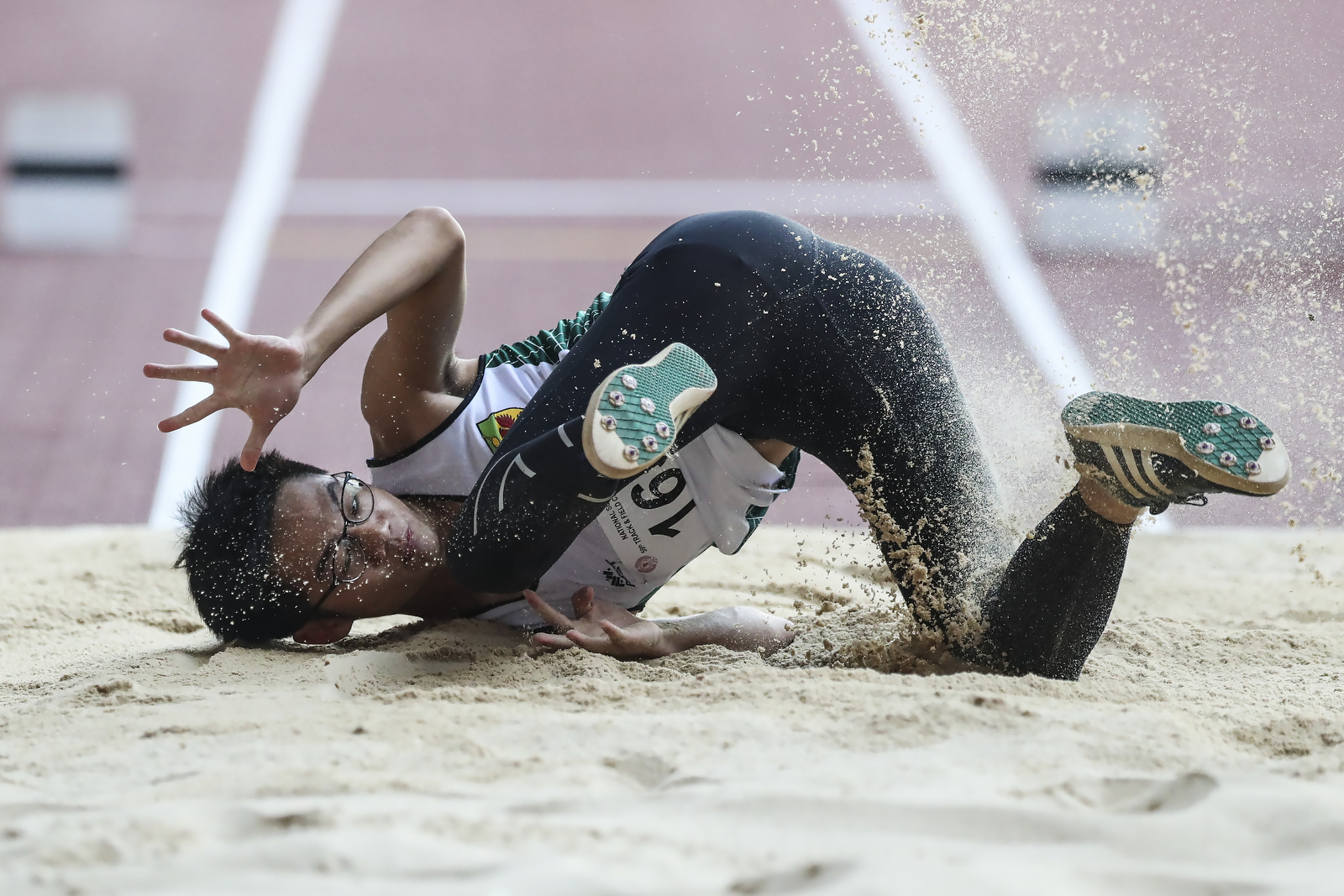 Ryan Lim of Raffles Institution falls on his attempt during the National Schools boys' 'A' Division boys' triple jump final at the National Stadium on April 11, 2018 in Singapore. (Photo © Yong Teck Lim/Red Sports)