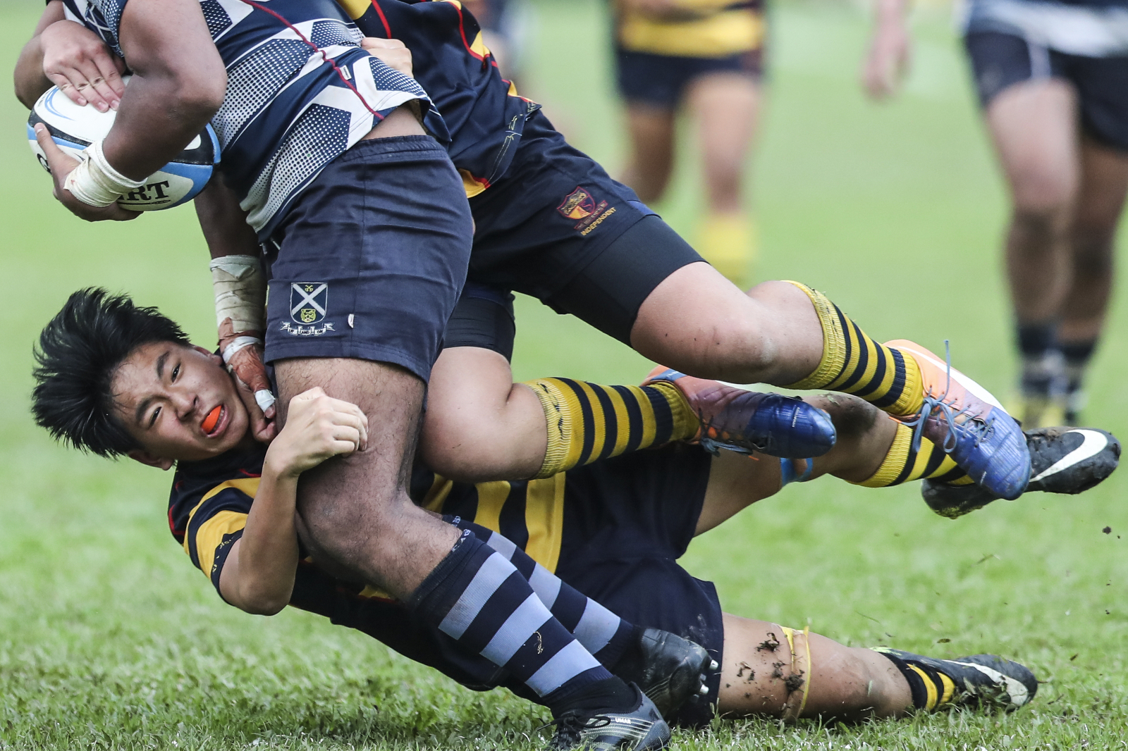Iain Yeow of Anglo-Chinese School (Independent) falls after a tackle on Umar Mohamed Sha'ari of St. Andrew's Secondary School during the National Schools boys' 'B' Division rugby final at Queenstown Stadium on March 28,2018 in Singapore. (Photo © Yong Teck Lim/Red Sports)