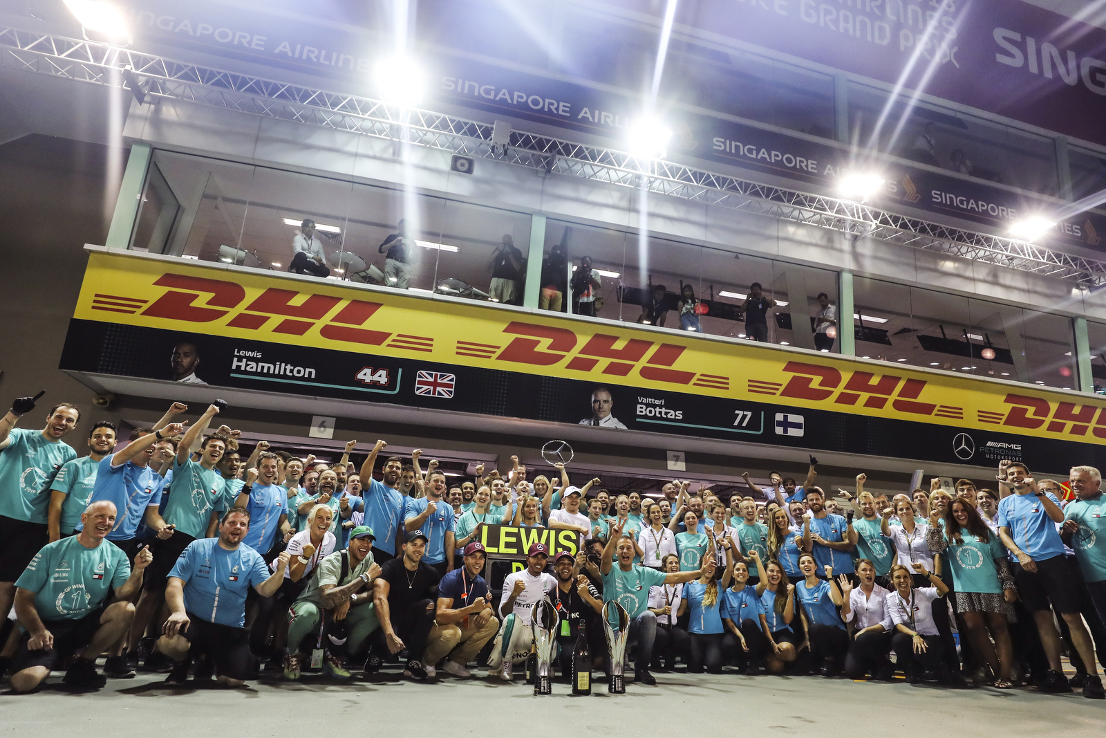 The Mercedes team poses for photos after Lewis Hamilton of Britain, center, wins the Singapore Formula One Grand Prix at the Marina Bay City Circuit in Singapore, Sunday, Sept. 16, 2018. (AP Photo/Yong Teck Lim)