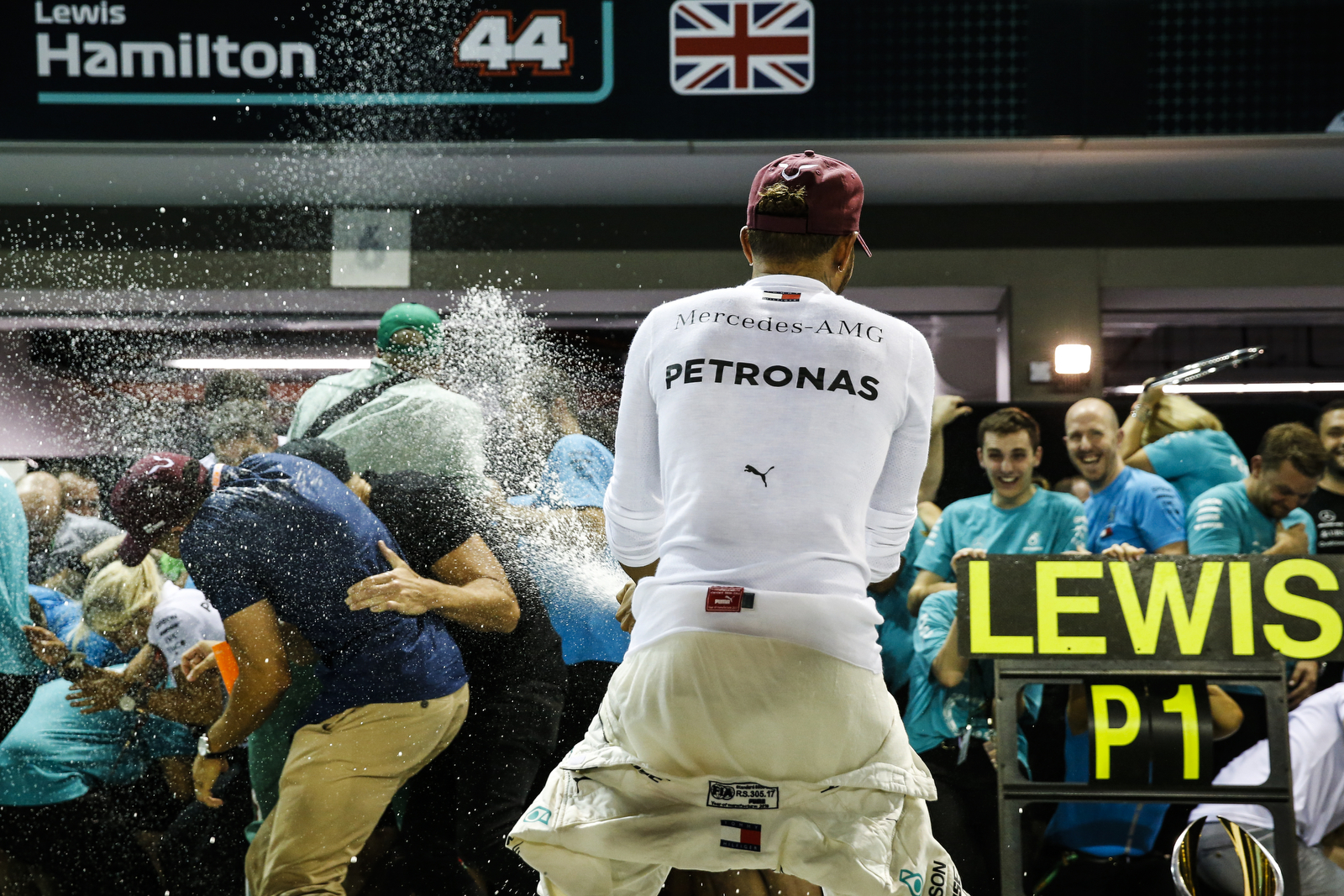 Mercedes driver Lewis Hamilton of Britain sprays champagne as he celebrates with his team after winning the Singapore Formula One Grand Prix at the Marina Bay City Circuit in Singapore, Sunday, Sept. 16, 2018. (AP Photo/Yong Teck Lim)