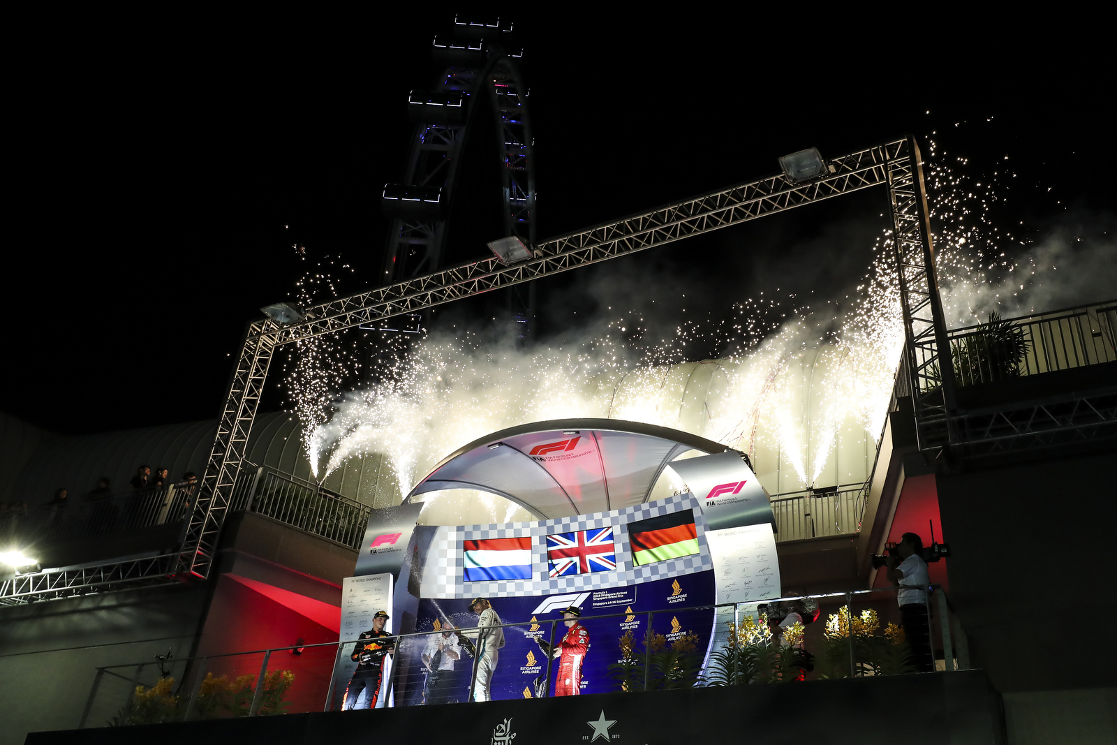 Mercedes driver Lewis Hamilton of Britain, center, sprays champagne as he celebrates after winning the Singapore Formula One Grand Prix, next to Ferrari driver Sebastian Vettel of Germany, right, and Red Bull Racing driver Max Verstappen at the Marina Bay City Circuit in Singapore, Sunday, Sept. 16, 2018. (AP Photo/Yong Teck Lim)
