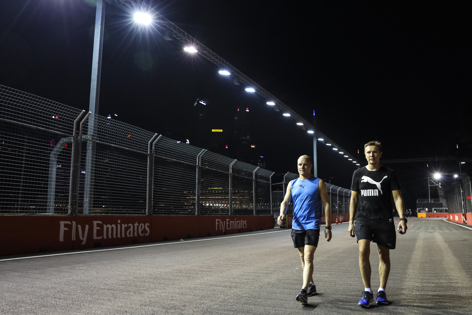 Mercedes driver Valtteri Bottas, left, of Finland walks the Marina Bay City Circuit track with his personal trainer, Antti Vierula, ahead of the Singapore Formula One Grand Prix in Singapore, Thursday, Sept. 13, 2018. (AP Photo/Yong Teck Lim)
