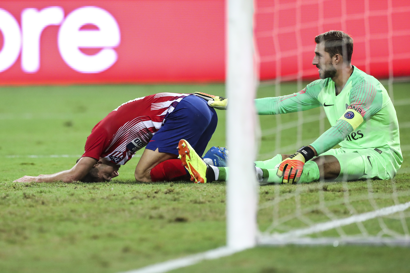 Paris Saint-Germain's Gianluigi Buffon, right, consoles Atletico Madrid's Luciano Vietto after the International Champions Cup match between Paris Saint-Germain and Atletico Madrid in Singapore, Monday, July 30, 2018. (AP Photo/Yong Teck Lim)