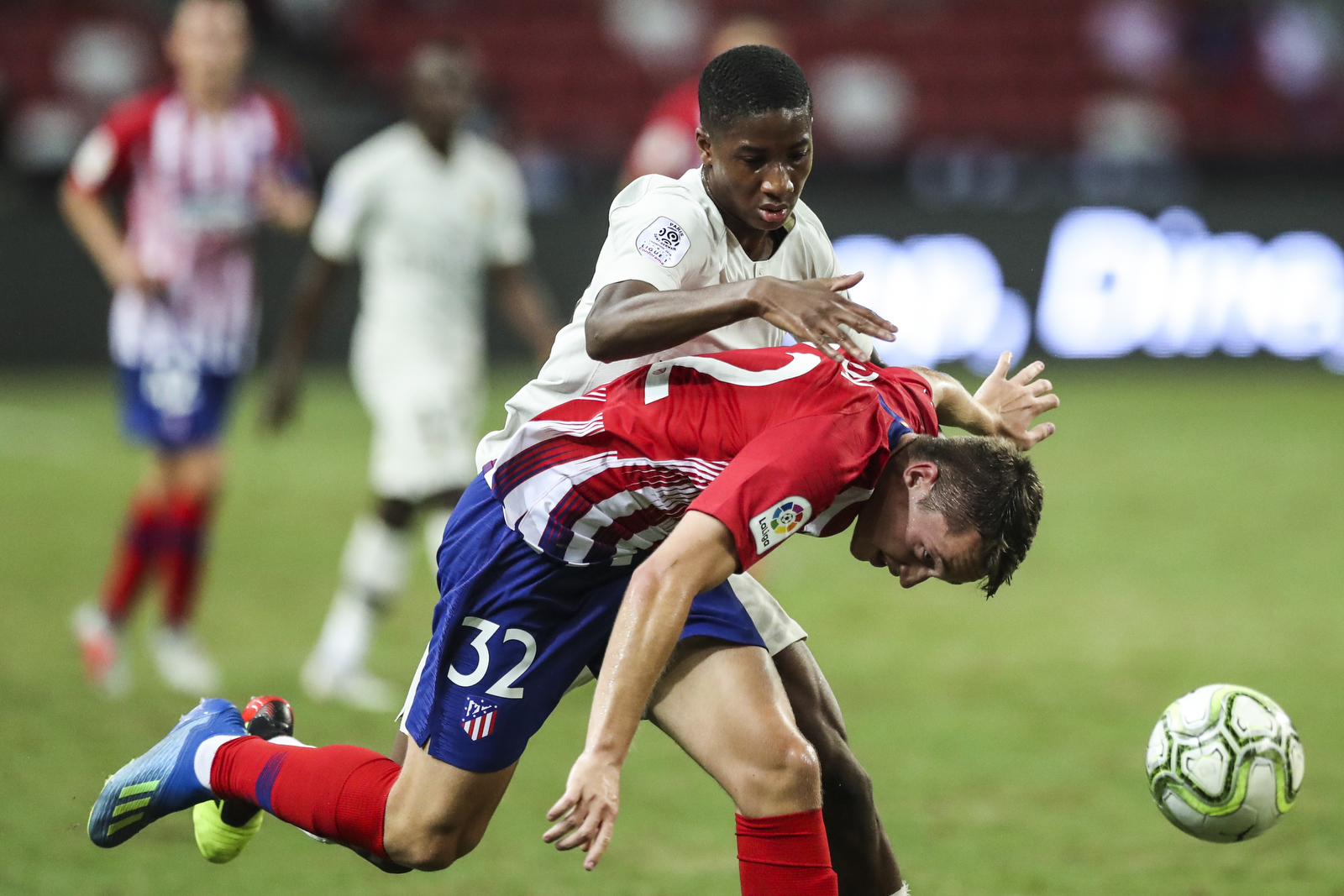 Atletico Madrid's Borja Garces, bottom, is fouled by Paris Saint-Germain's Moussa Sissako during the International Champions Cup match between Paris Saint-Germain and Atletico Madrid in Singapore, Monday, July 30, 2018. (AP Photo/Yong Teck Lim)