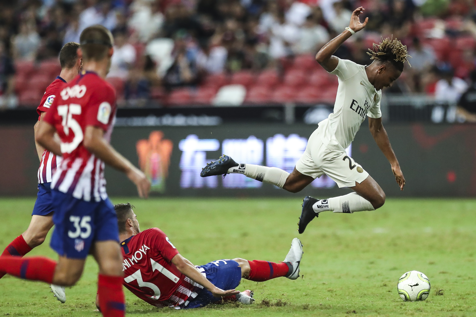 Paris Saint-Germain's Christopher Nkunku jumps to avoid a tackle by Atletico Madrid's Toni Moya during the International Champions Cup match between Paris Saint-Germain and Atletico Madrid in Singapore, Monday, July 30, 2018. (AP Photo/Yong Teck Lim)