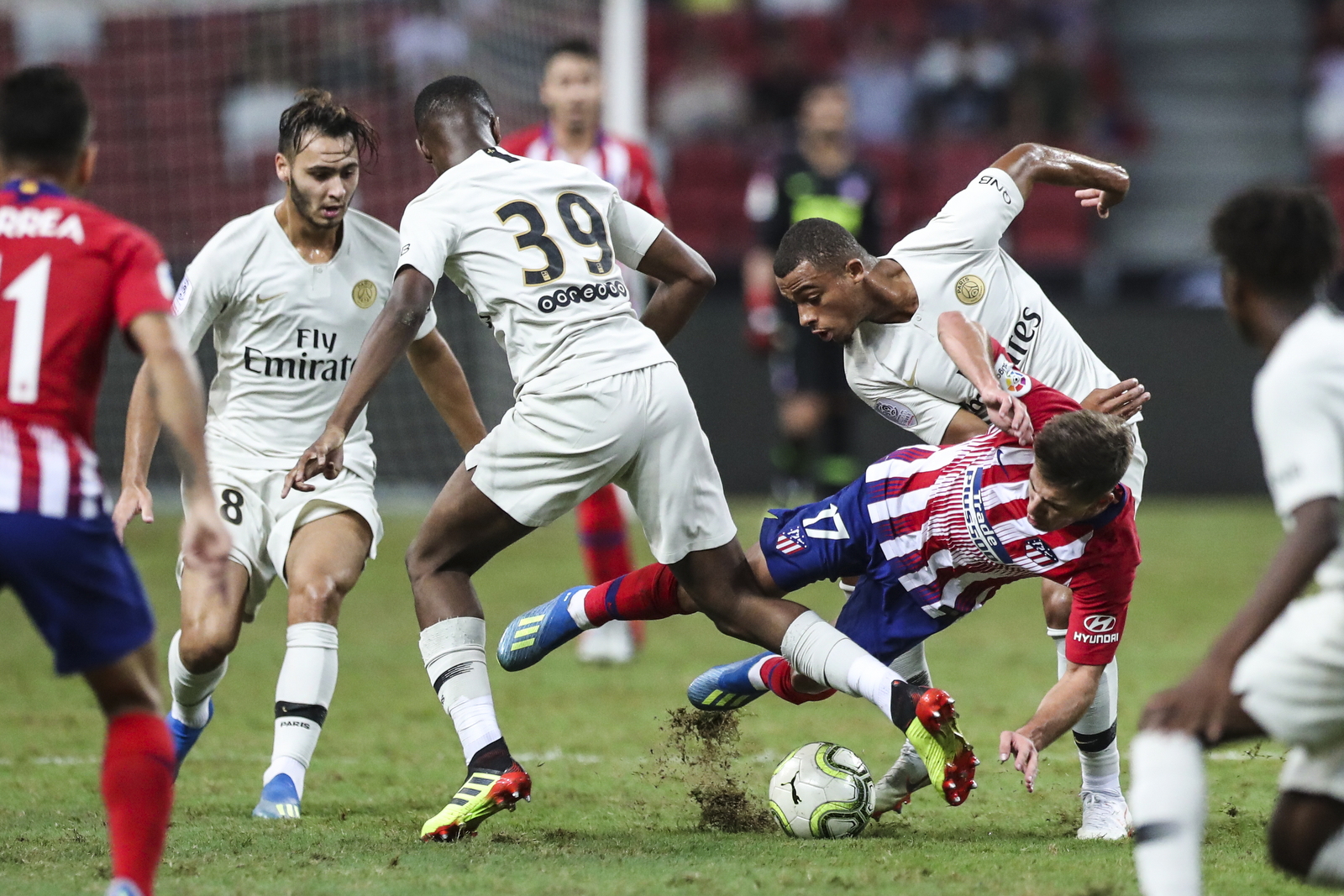 Atletico Madrid's Luciano Vietto falls after a tackle by Paris Saint-Germain's Antoine Bernede, right, and Moussa Sissako during the International Champions Cup match between Paris Saint-Germain and Atletico Madrid in Singapore, Monday, July 30, 2018. (AP Photo/Yong Teck Lim)