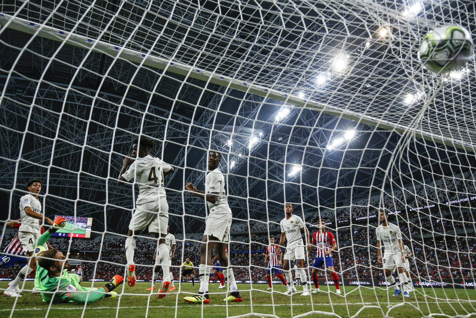 Atletico Madrid's Victor Mollejo, left, scores their first goal during the International Champions Cup match between Paris Saint-Germain and Atletico Madrid in Singapore, Monday, July 30, 2018. (AP Photo/Yong Teck Lim)