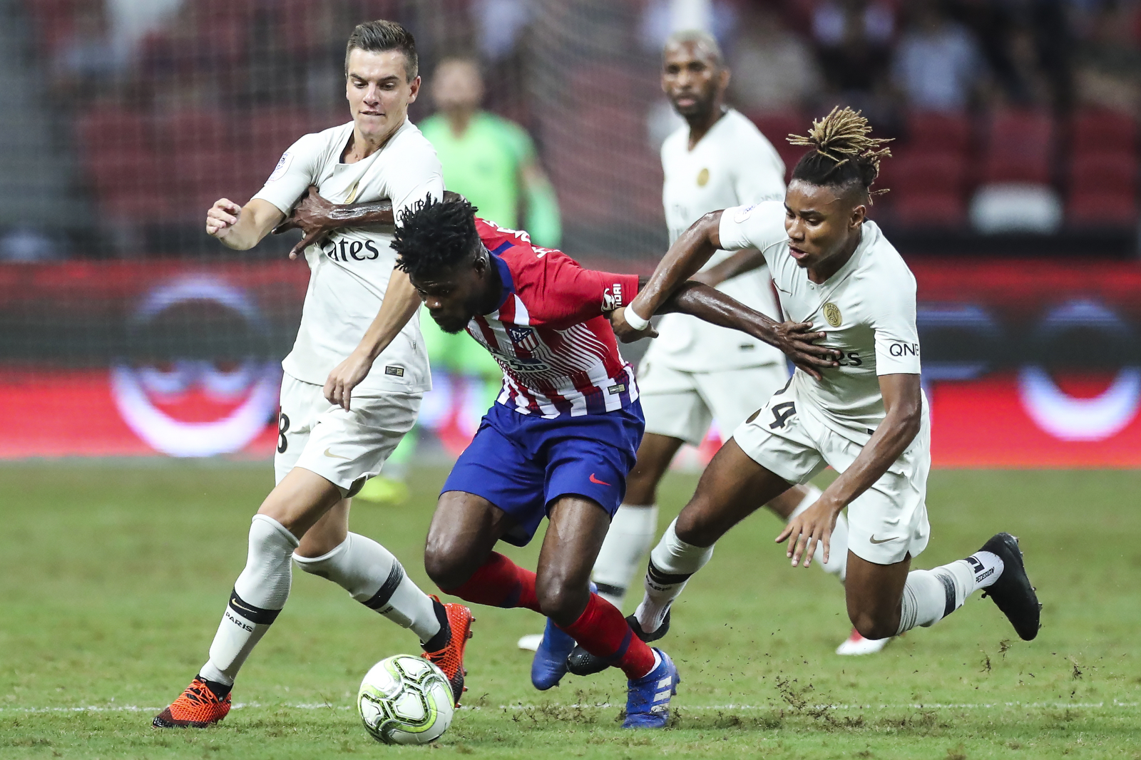 Atletico Madrid's Thomas Partey, center, controls the ball against Paris Saint-Germain's Giovani Lo Celso, left, and Christopher Nkunku  during the International Champions Cup match between Paris Saint-Germain and Atletico Madrid in Singapore, Monday, July 30, 2018. (AP Photo/Yong Teck Lim)