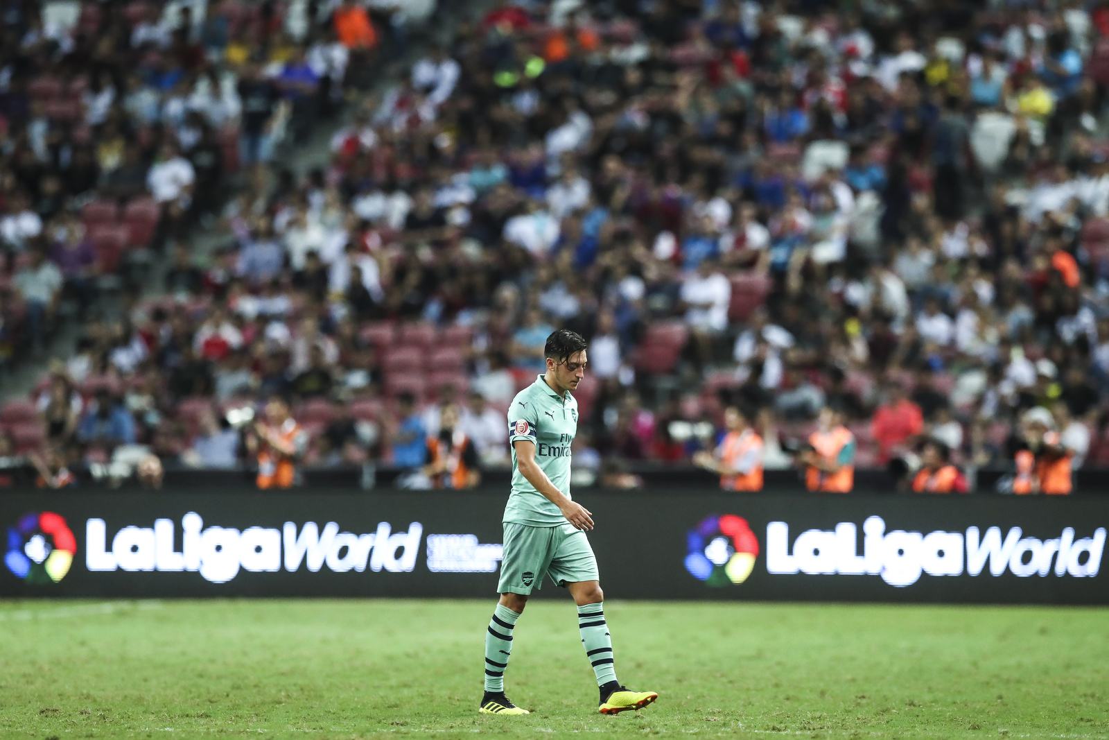 Arsenal's Mesut Ozil walks off the pitch after being substituted during the International Champions Cup match between Arsenal and Paris Saint-Germain in Singapore, Saturday, July 28, 2018. (AP Photo/Yong Teck Lim)
