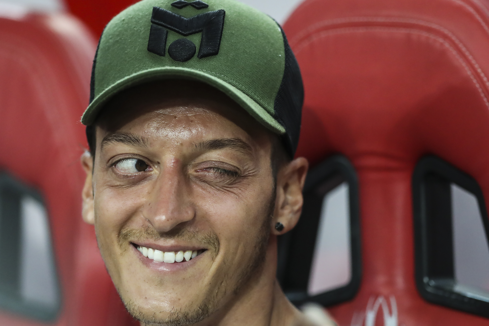 Arsenal's Mesut Ozil winks to a teammate on the bench during the International Champions Cup match between Arsenal and Atletico Madrid in Singapore, Thursday, July 26, 2018. (AP Photo/Yong Teck Lim)