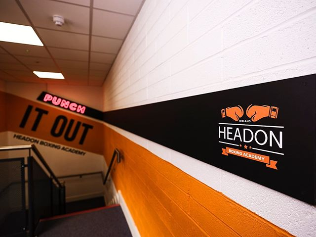The blackboard entrance leading line starts with a Neon Punch and ends with the Headon Boxing Academy logo, also functioning as a notice board for class schedules. The main room is wrapped with an orange stripe that is capped with backlit HBA letters made of textured gym matts. . . . #gym #design #orange #black #branding