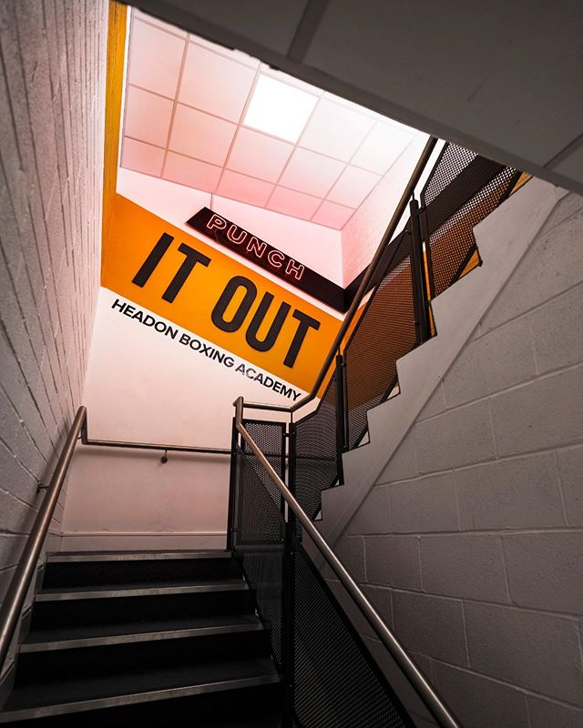 """We finished the installation in the new @headonboxingacademy boxing gym at Landsdowne this week. A single orange leading line brings people from the entrance up the stairway and through the main gym room. Along the way there are designs made of both cut out gym matts (some of which are backlit) and neon, starting with a motivational """"Punch It Out"""" instagram wall. . . . #gym #design #orange #neon #interior"""