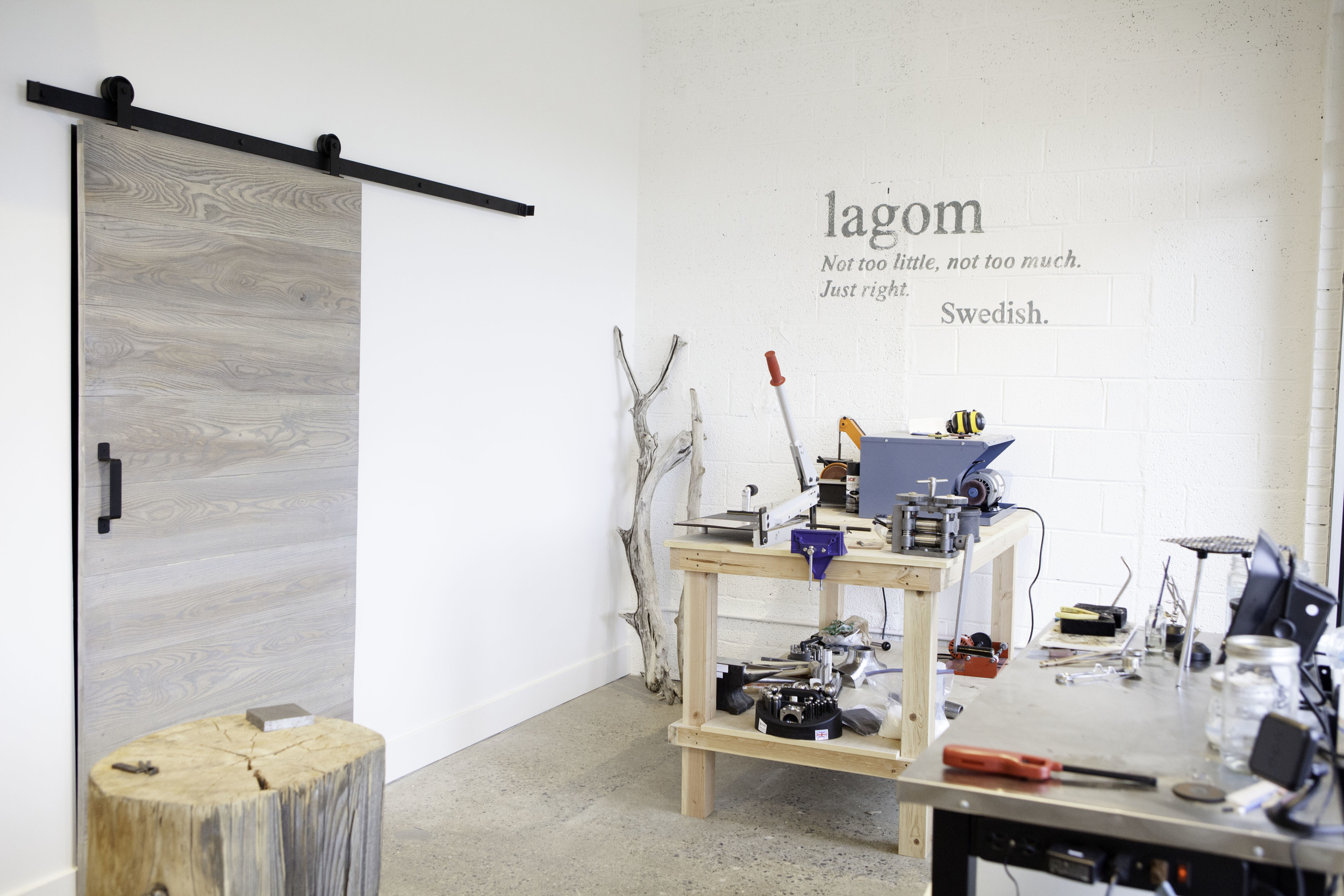 "My open workshop. The stump I found in Idaho where I hammer, the workbench in the back that houses my many tools and machines, the soldering station to the right, the sliding barndoor that goes into my storage room and the hand painted Swedish saying of ""Lagom"" on the wall."