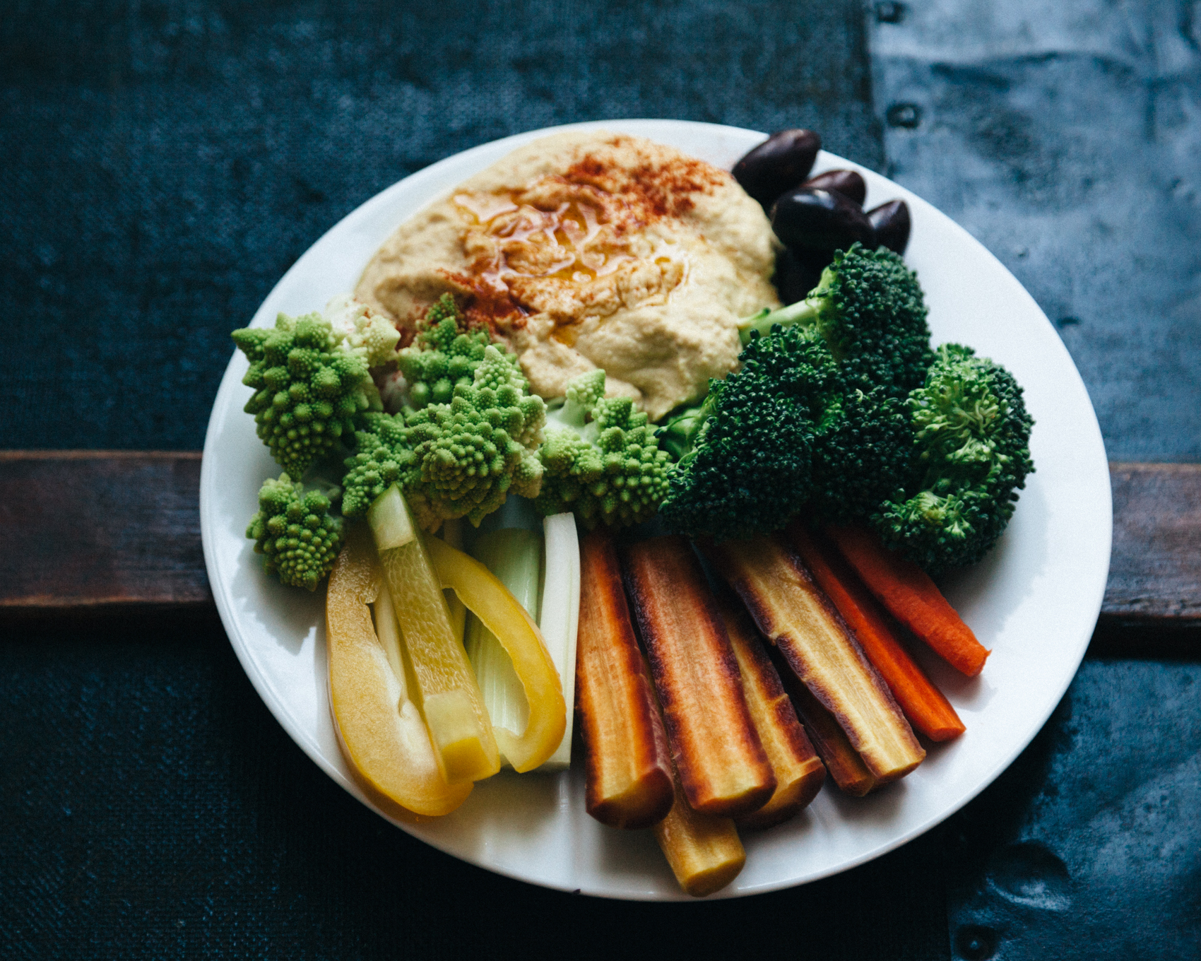 Roasted red pepper hummus garnished with a dollop of olive oil and a sprinkling of paprika, with a side of kalamata olives, romanesco, yellow peppers, celery, carrots and broccoli.