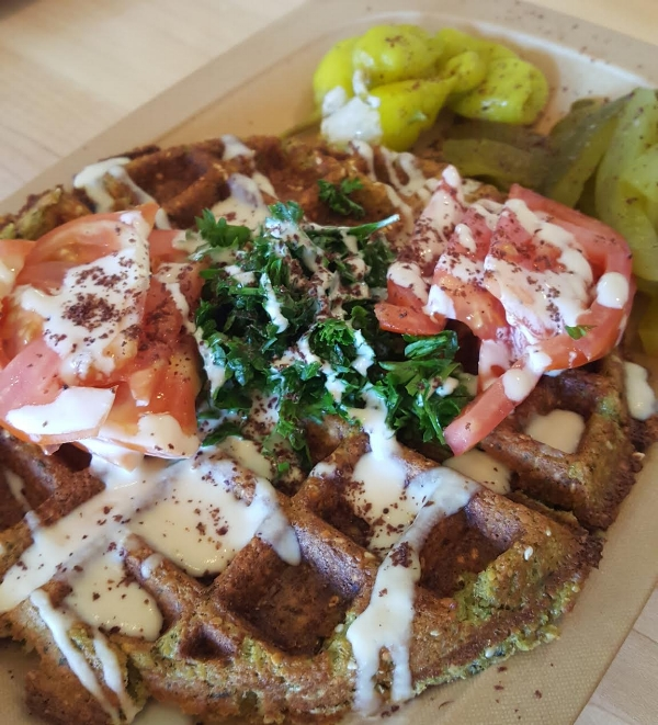 Chickpea's Fawaffle topped with tahini, fresh parsley, tomatoes, and paired with pickled peppers. Pure genius!