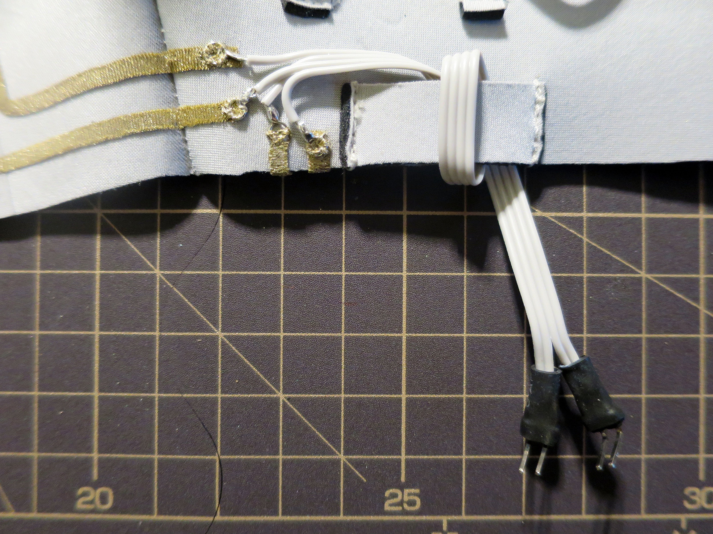 This glove controller instructable  (step 9) shows how to to solder cables with stitching loops and header pins