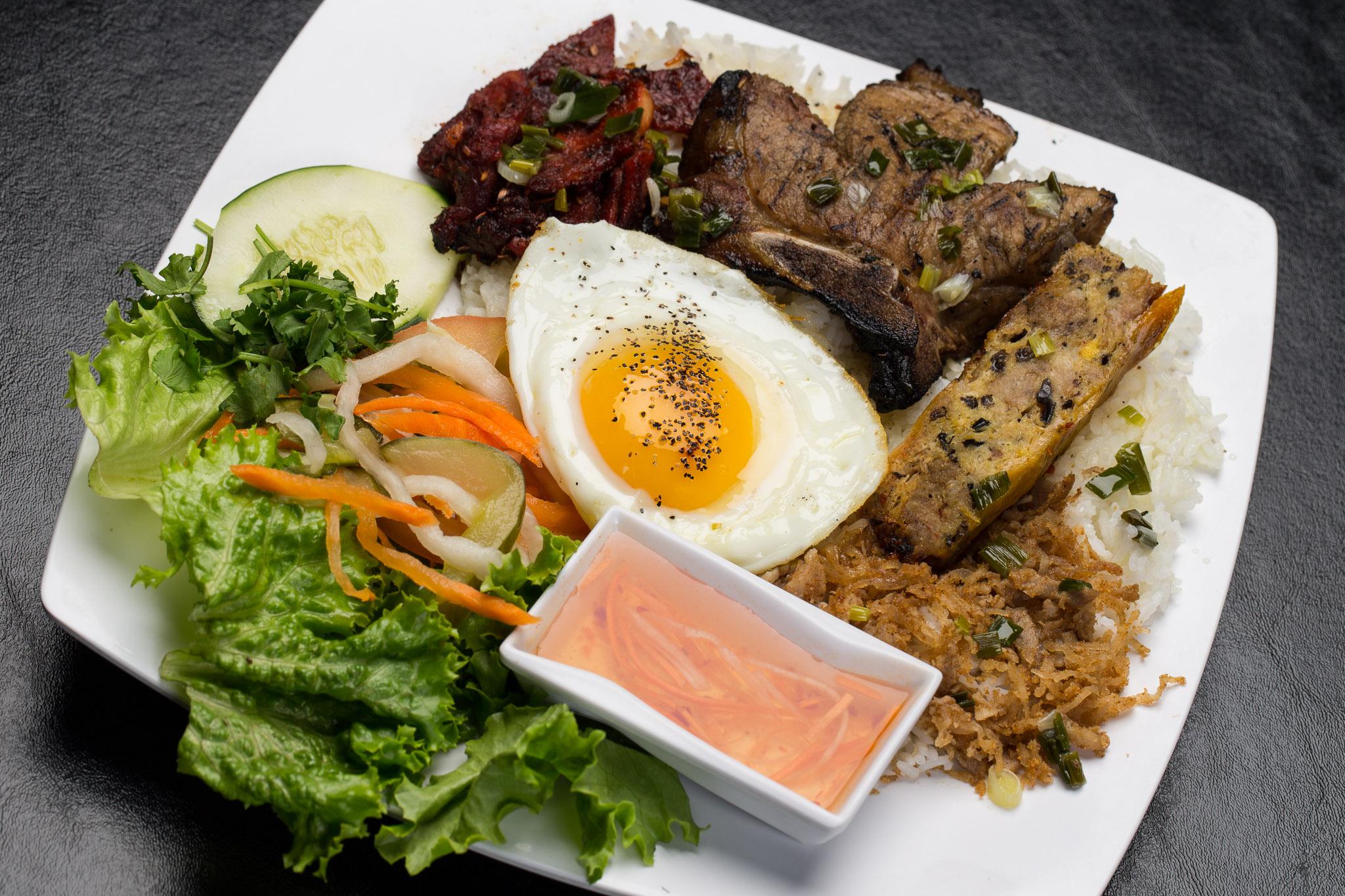 7.01 Com Dac Biet  | crushed rice platter topped with char-grilled pork, marinatedpork-chop, over-easy egg, egg-cake, & shredded pork served with sweet lemon sauce.