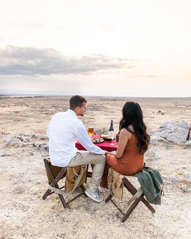 "I had to heavily edit this photo to make it look remotely close to how amazing this moment actually felt. Sitting on top of the highest point outside of Tarangire National Park, enjoying the cool breeze after an otherwise warm day, stuffing our faces with delicious snacks, and sipping on amazing wine. The sunset wasn't the clearest but it was breathtaking nonetheless. SWIPE to see ""behind the scenes"". Our guides laughed at me for setting up the tripod like this just to snap a few pics 🍻"