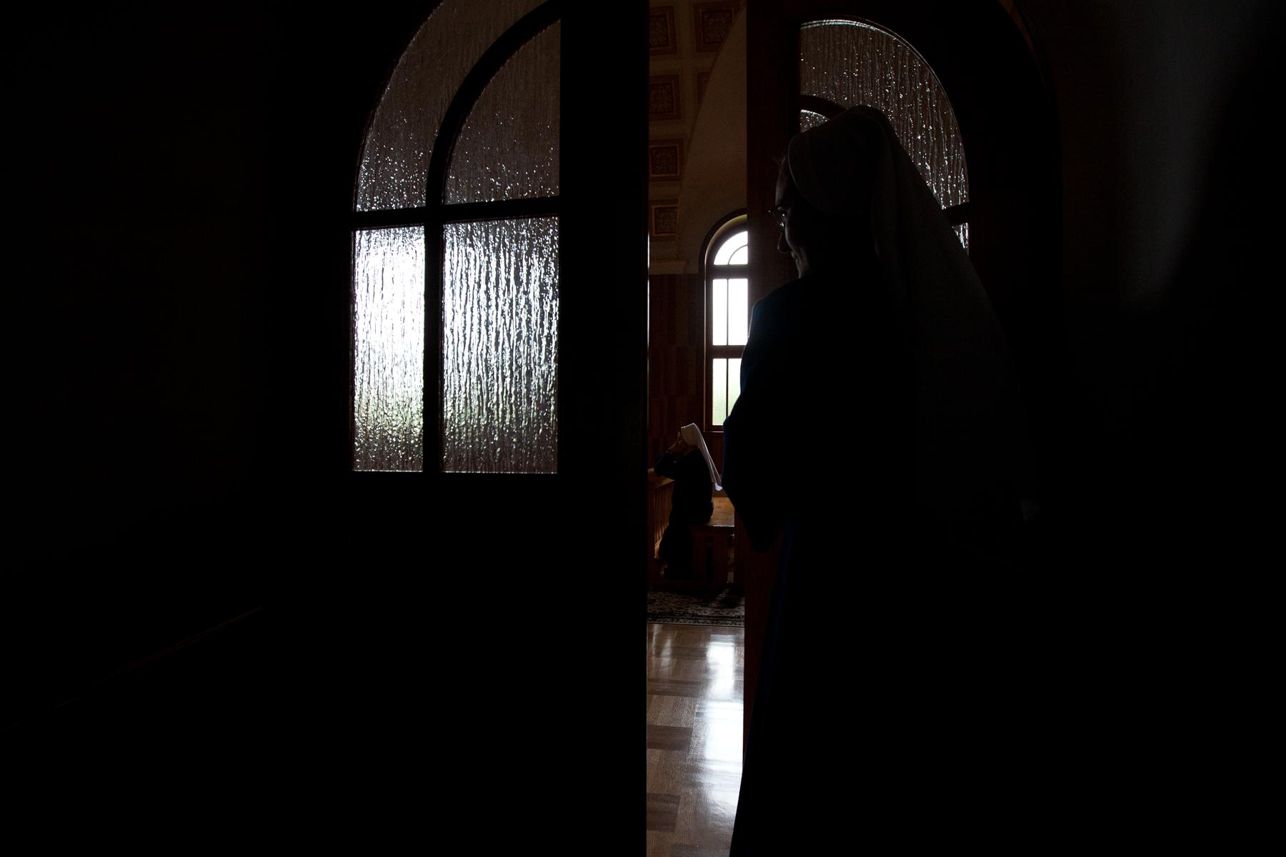 A catholic nun enters a convent chapel in southeast Poland.  Image ©Connor Stefanison