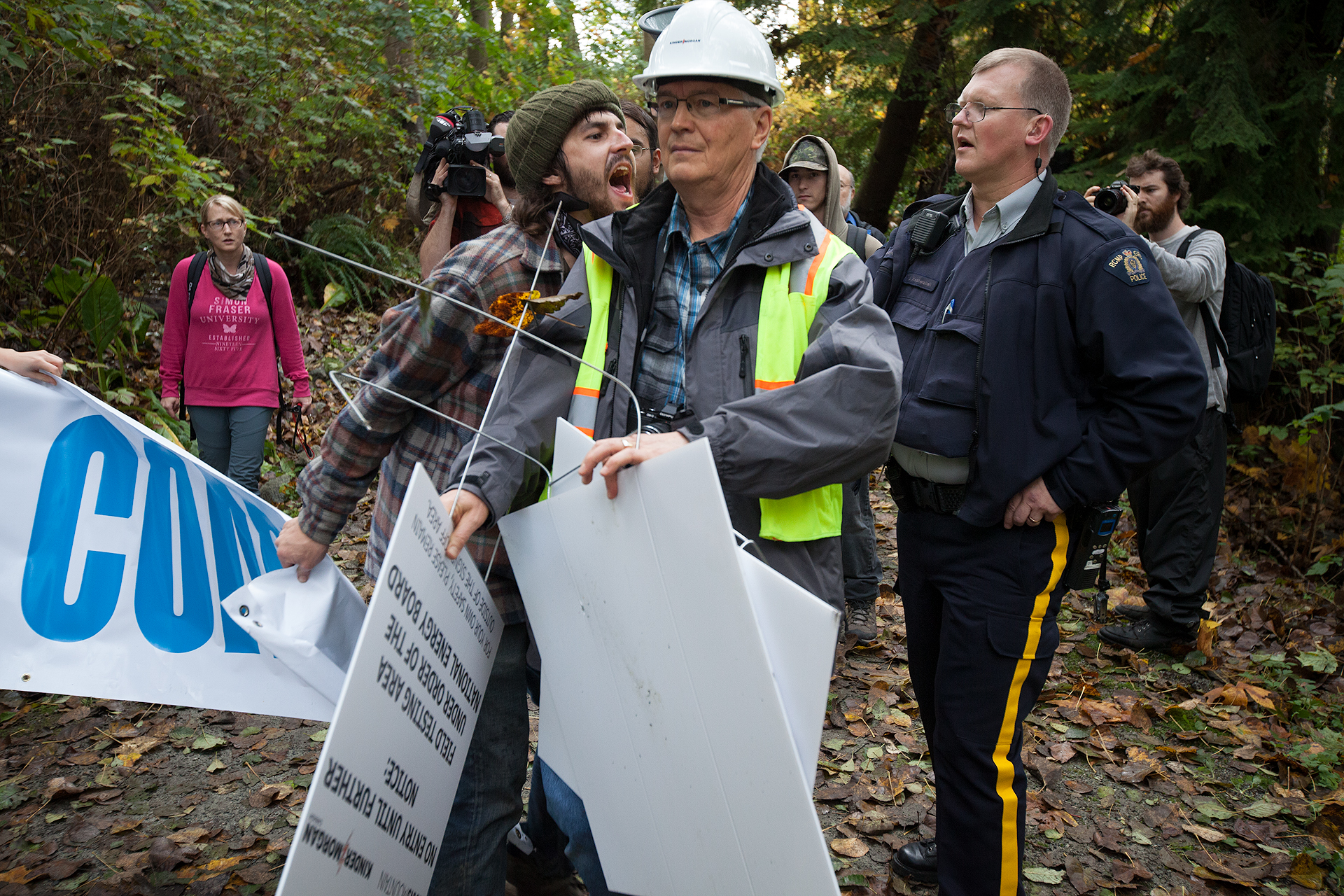 A protestor screams in anger after discovering Kinder Morgan employees once again illegally cutting vegetation in the conservation area.