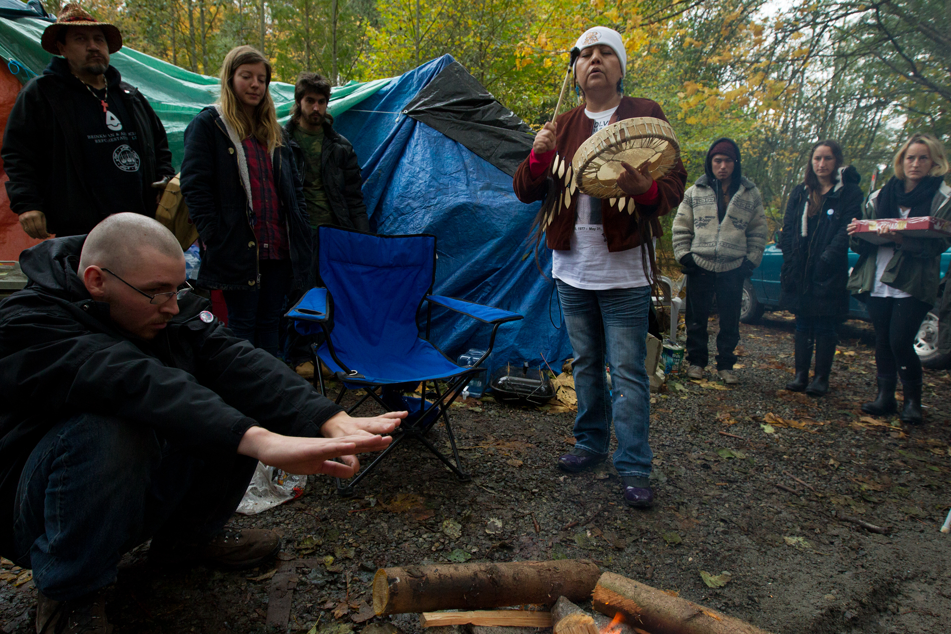 """A First Nations woman at a protest campdrums a song to initiate the """"Sacred Fire"""", a fire that would burn continuously for almost three months."""