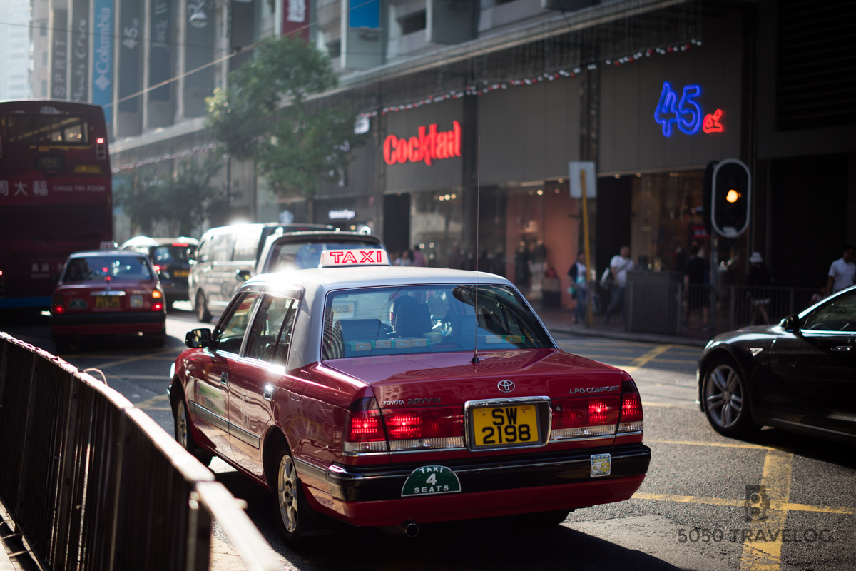 A sunny Saturday in Causeway Bay. The classic red Toyota Crown Comfort offer an affordable transportation option