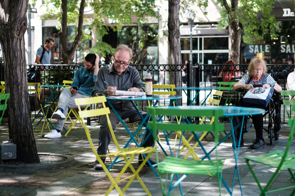 A man sits by a table in a Seattle Park doing a cross word puzzle
