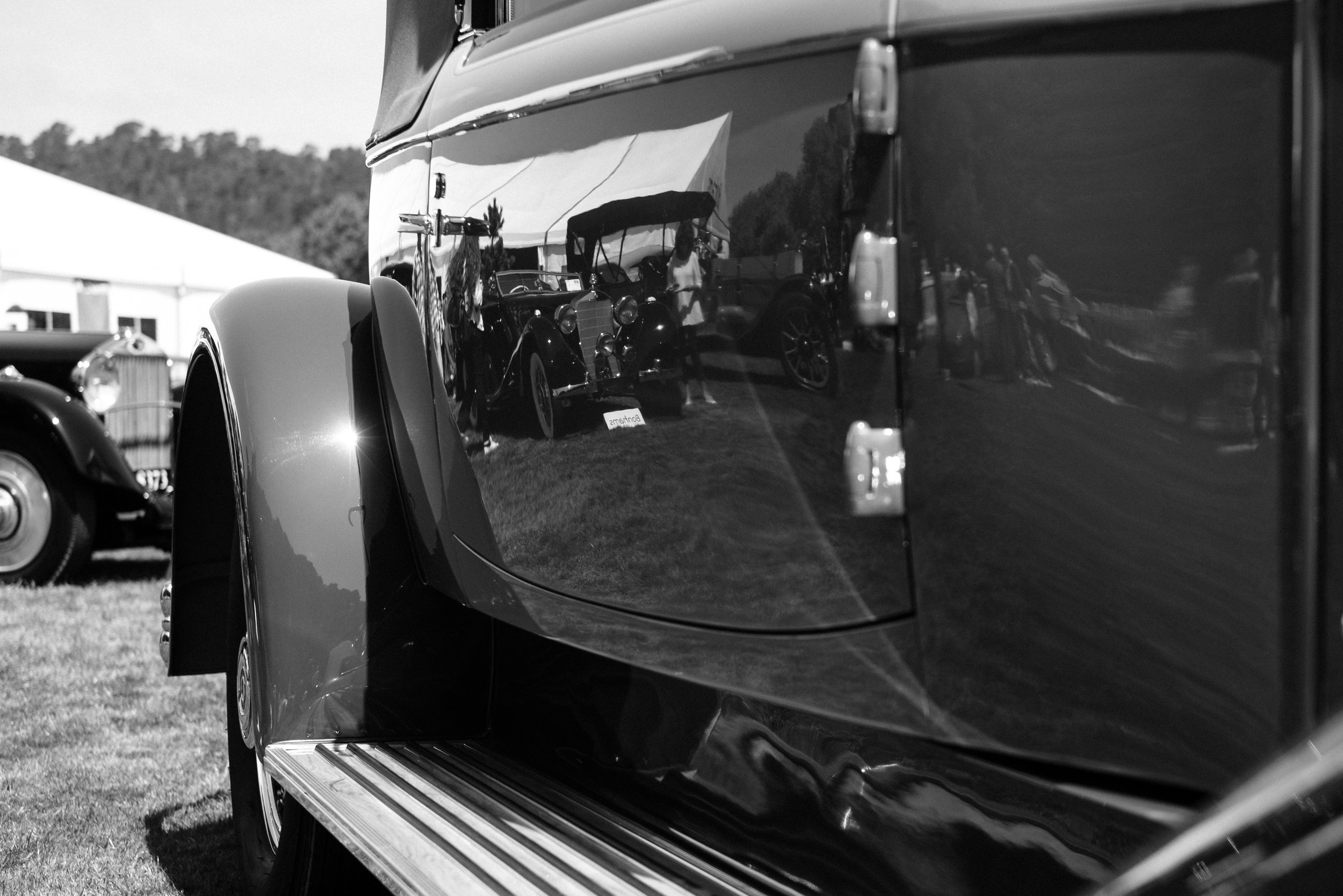 Reflections in a car door of vintage cars on display at Pebble Beach Concours in California, USA