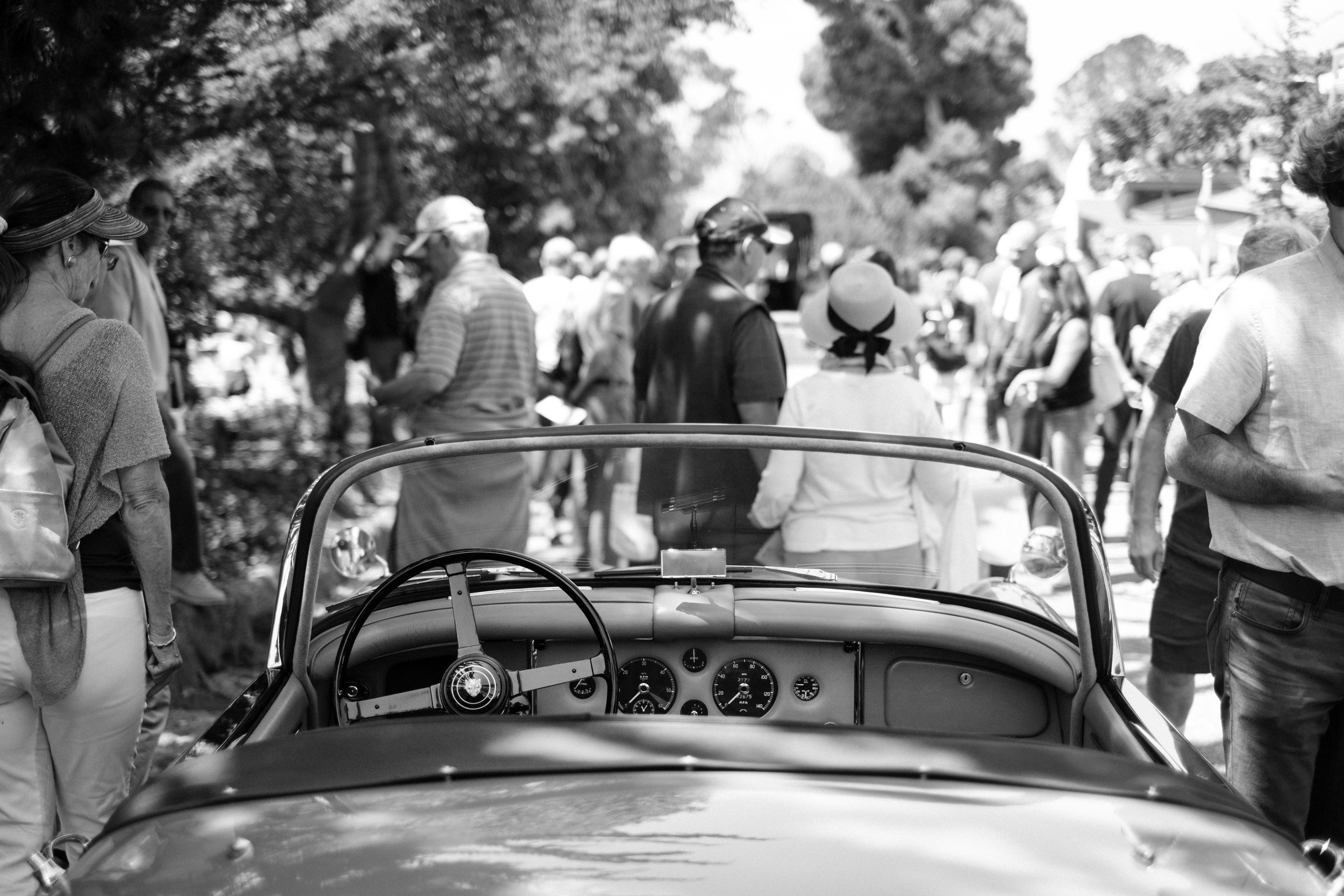 A classic sports car and crowds at Pebble Beach California