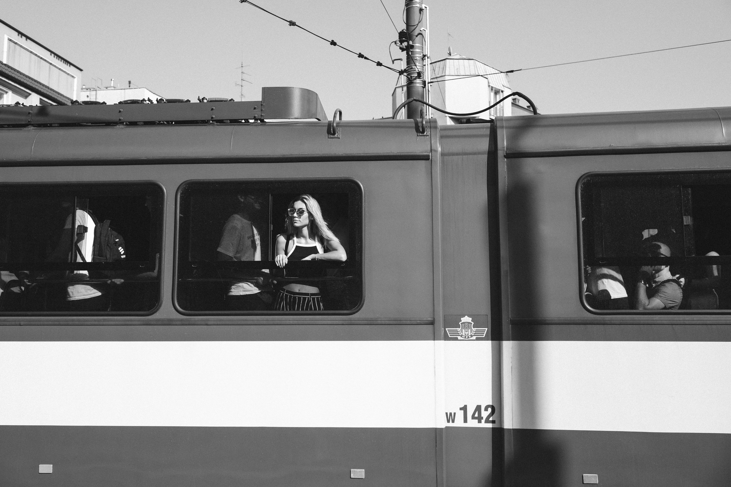 A young woman looks out the window from a tram on a summer day in Krakow Poland