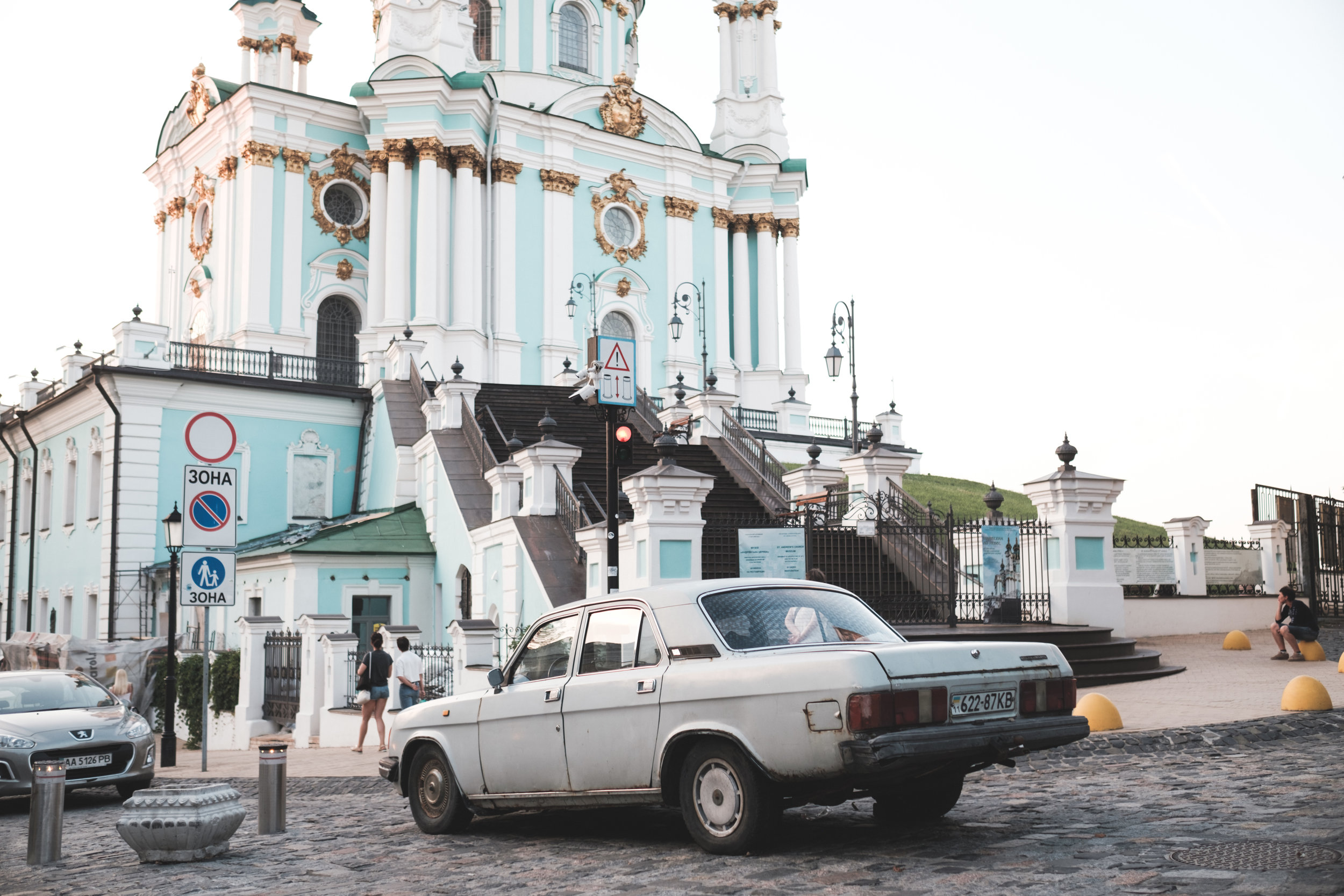 An old car is parked in front of St. Andrew's Cathedral in Kiev Ukraine